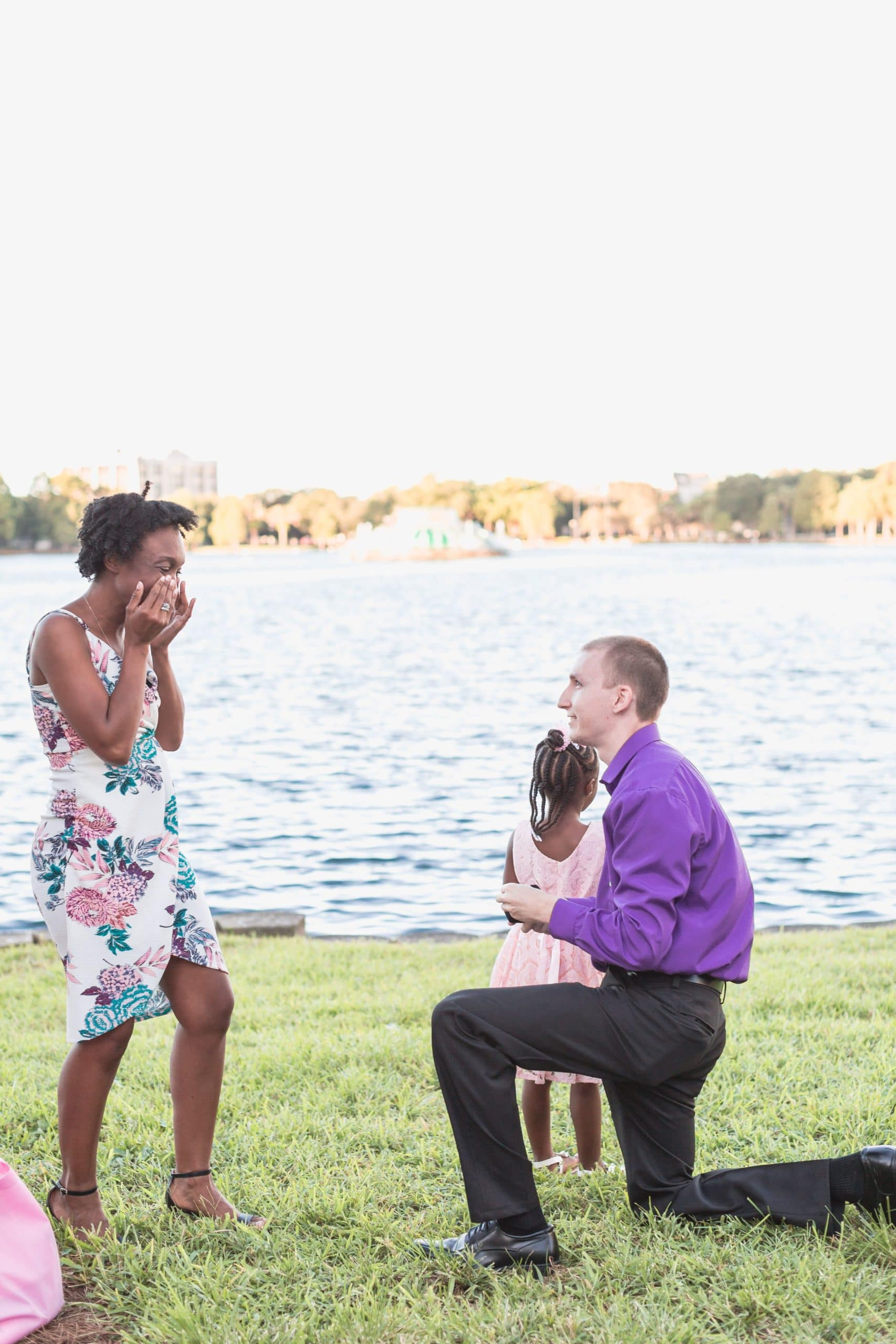 man in purple shirt on bended knee in front of lake proposing to woman in floral dress