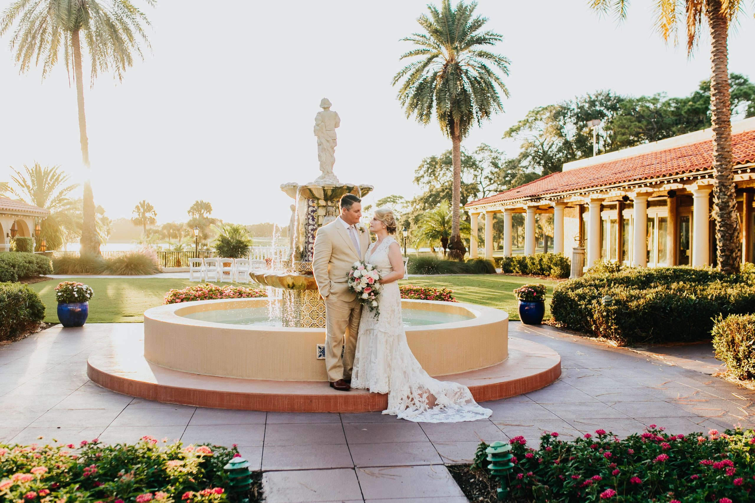 bride and groom standing in front of spanish style fountain for wedding portrait photo