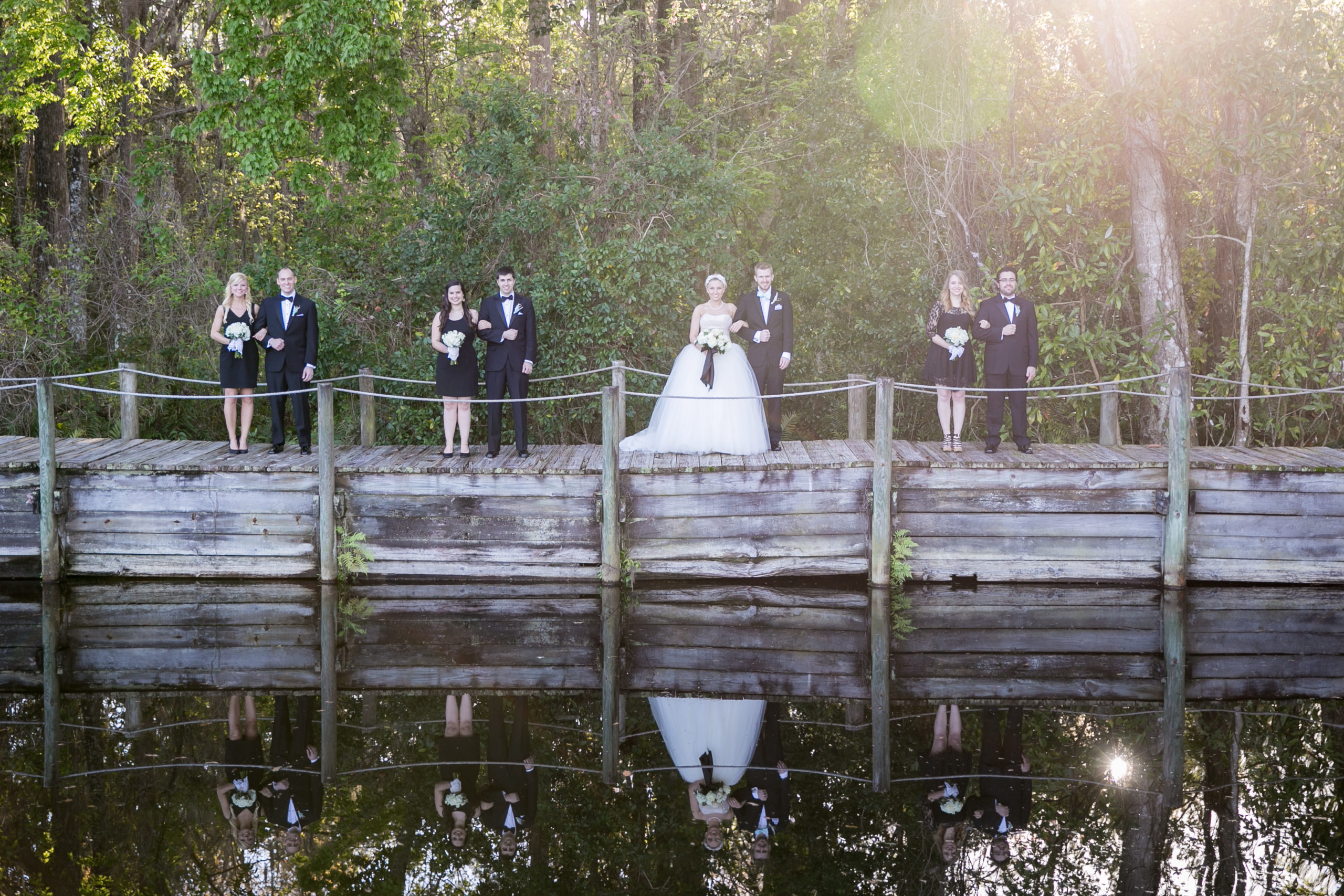 Bride and Groom standing on bridge with reflections in the water