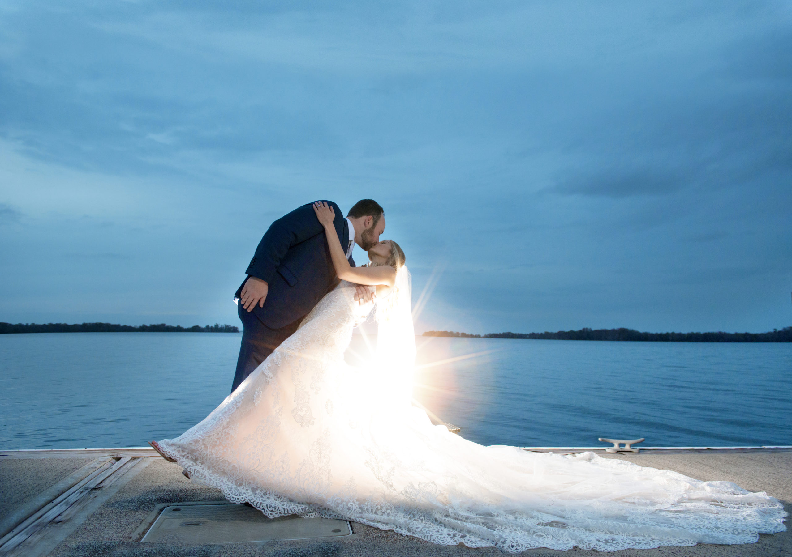 Bride being dipped by her groom at sunset on the docks of marina del rey on wedding day