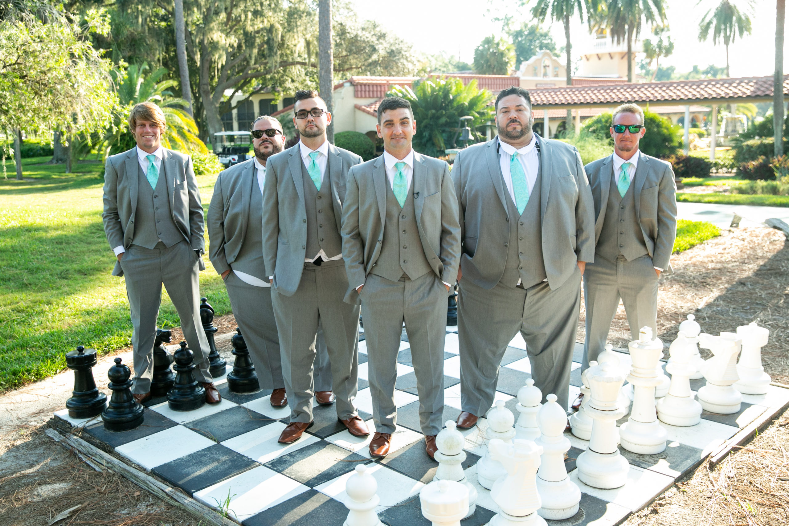 Groomsmen standing on giant chess board