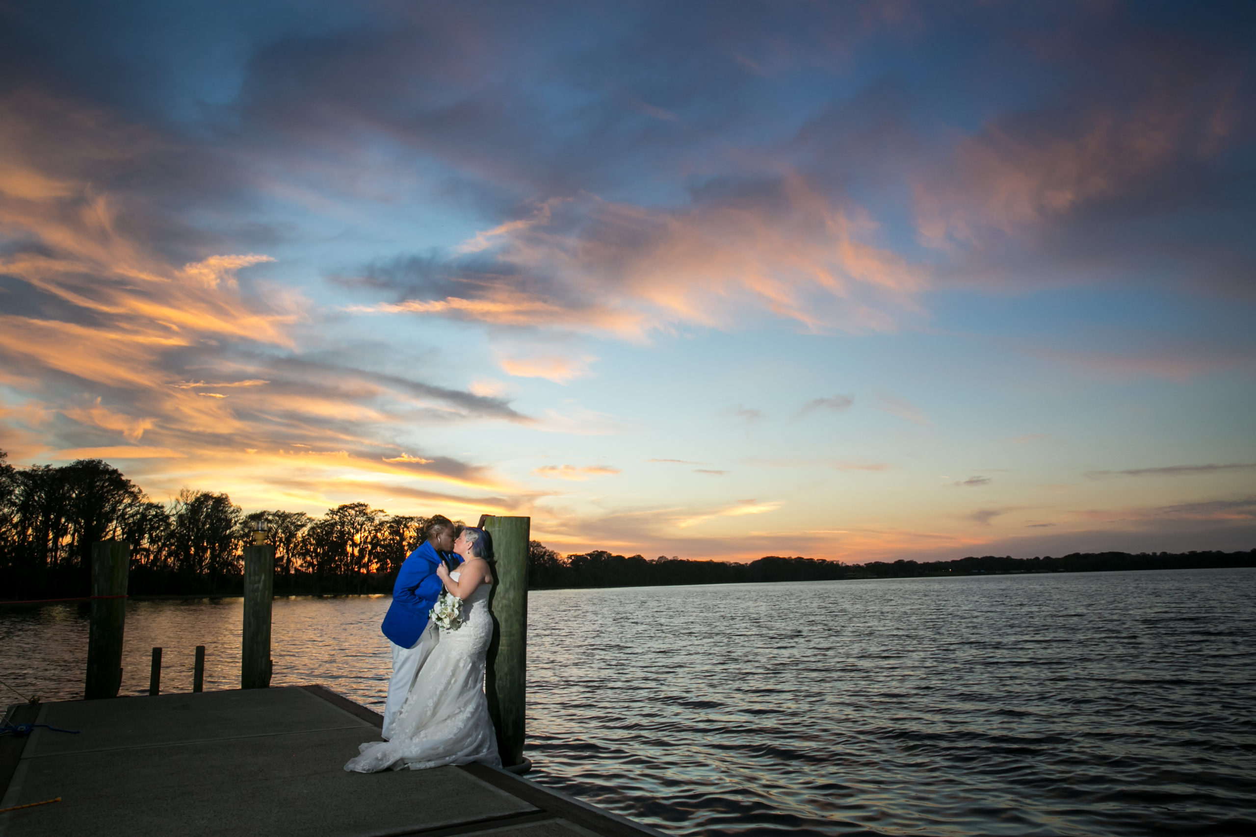 Bride in blue blazer kissing bride in wedding gown on the pier at mission inns marina del rey at sunset