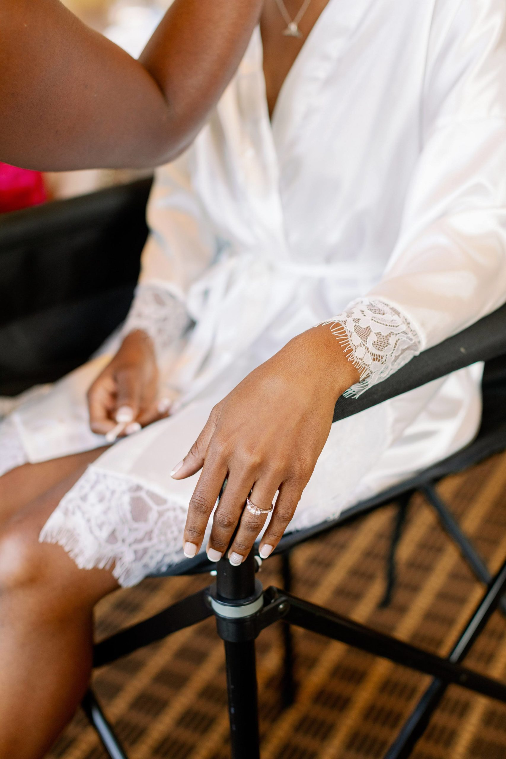 Bride sitting on black chair in white robe with hand showing engagement ring