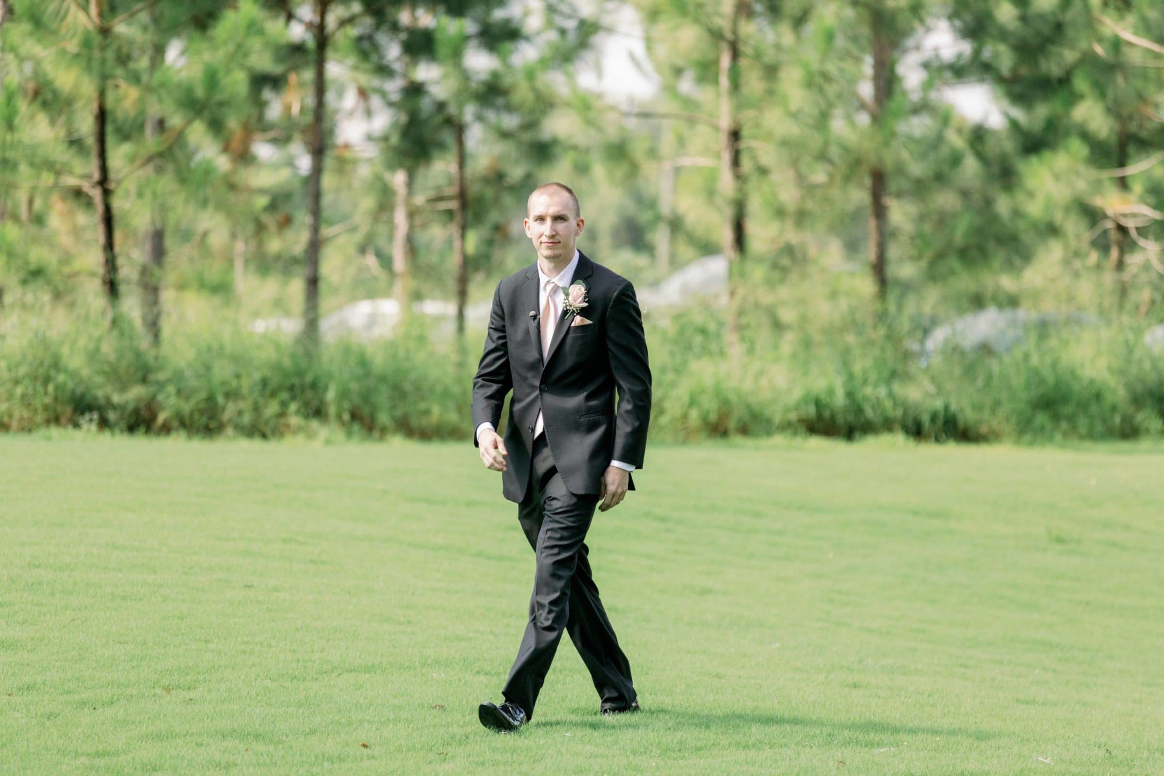 Groom walking in the grass for lakeside wedding ceremony