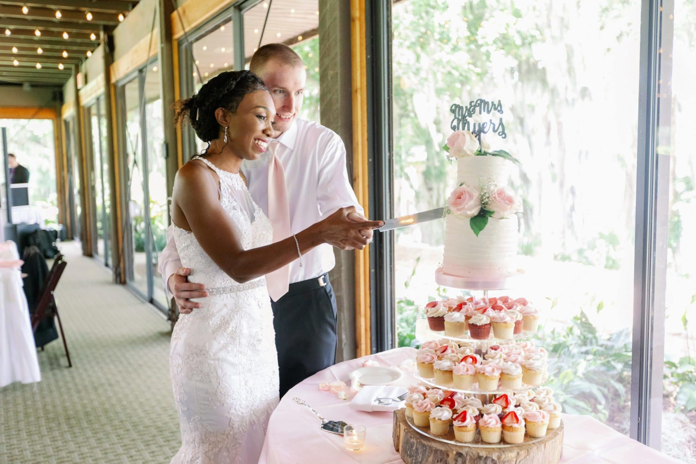 bride and groom cutting wedding cake in front of glass window overlooking lake