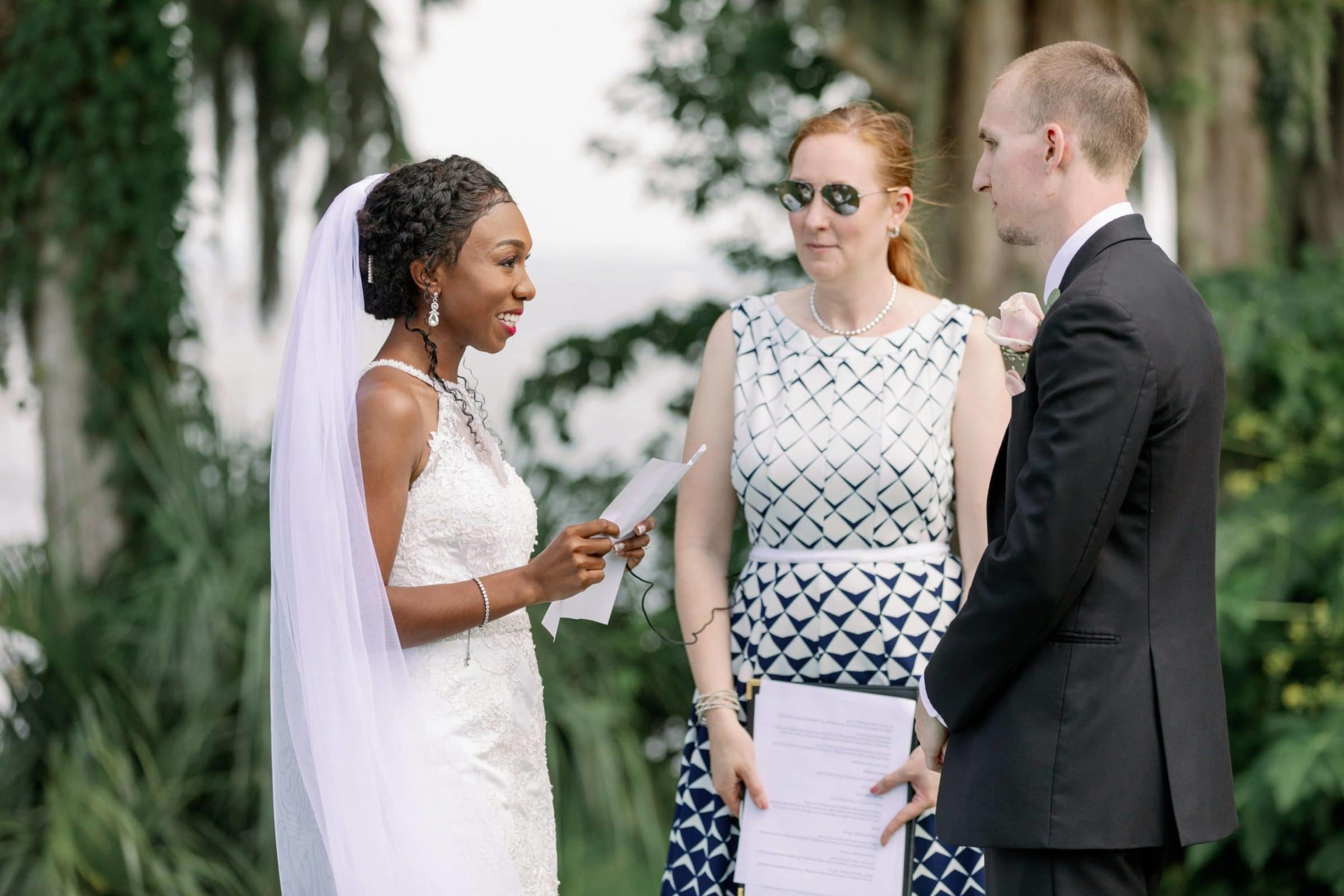 Bride and groom exchanging wedding vows with officiant lakeside