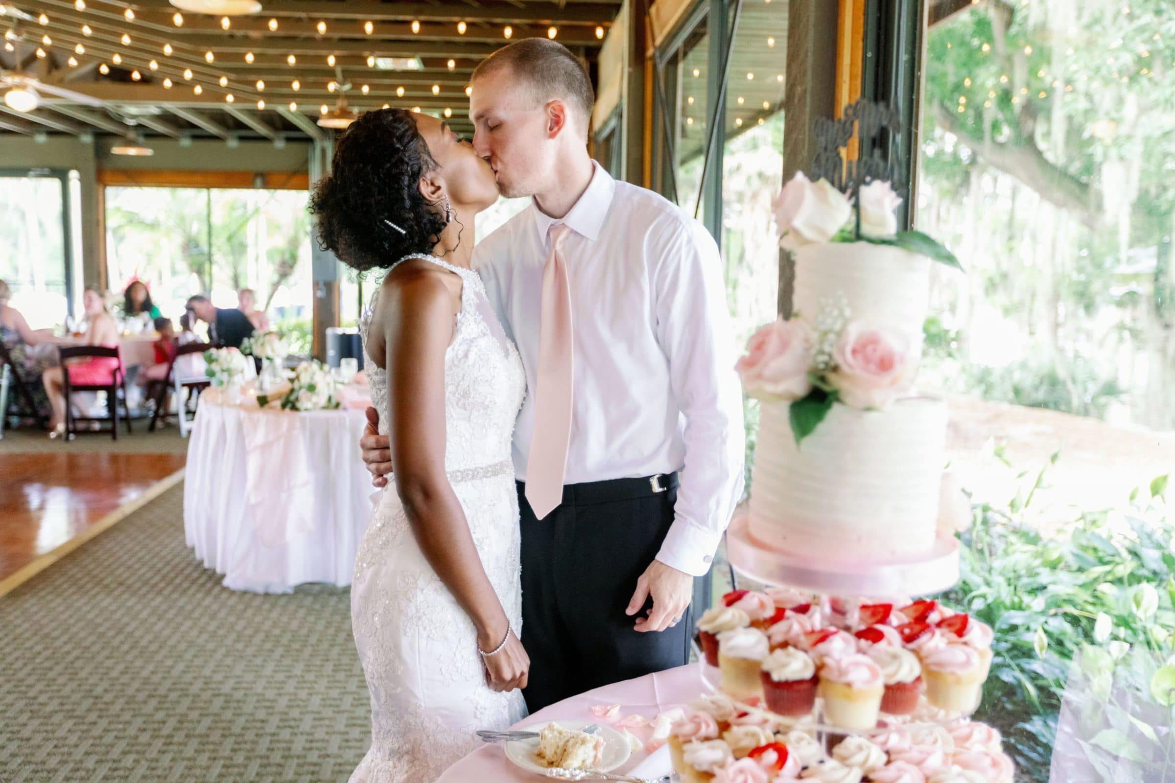 Bride and Groom kissing behind wedding cake and dessert