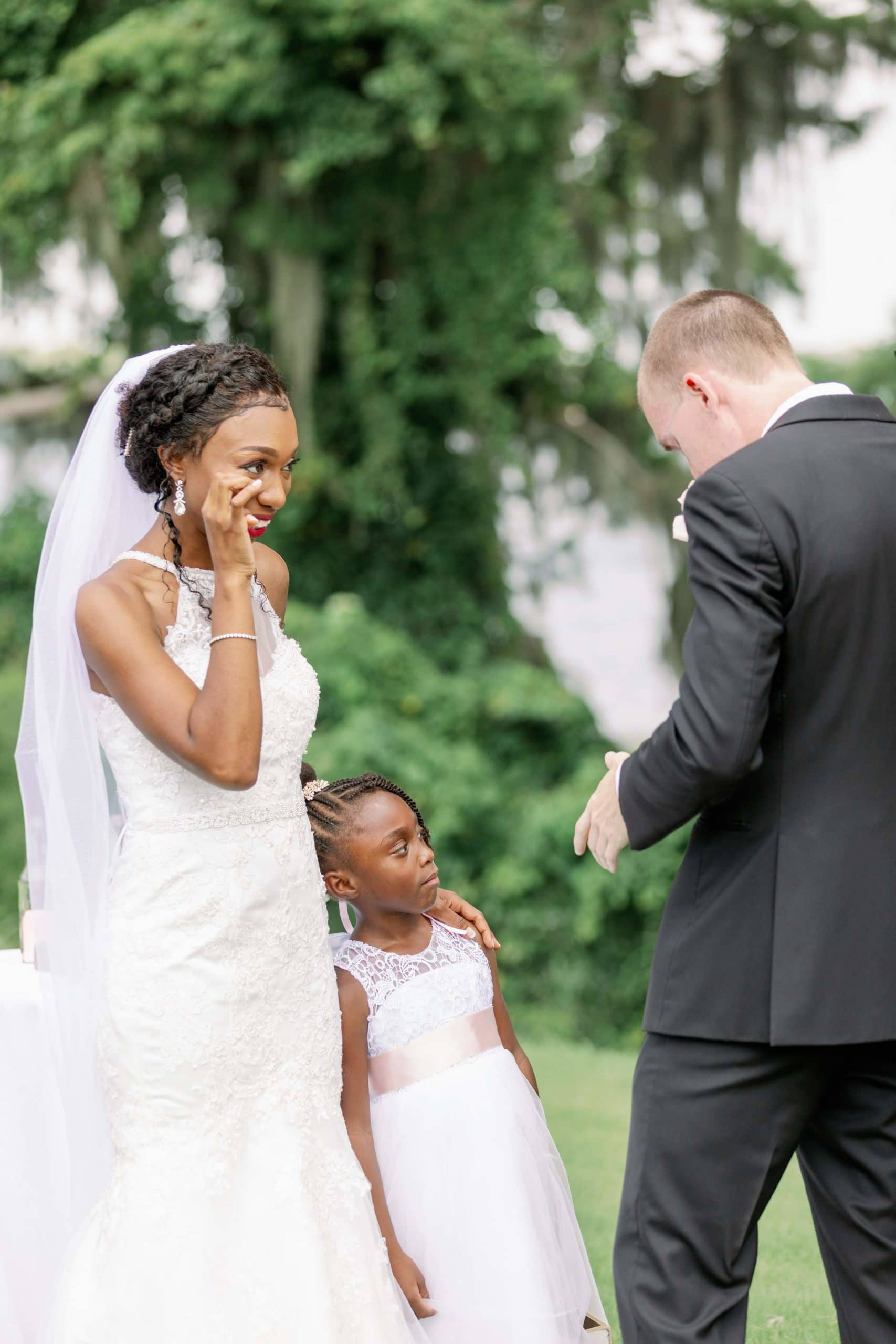 Bride, groom and flower girl during ceremony
