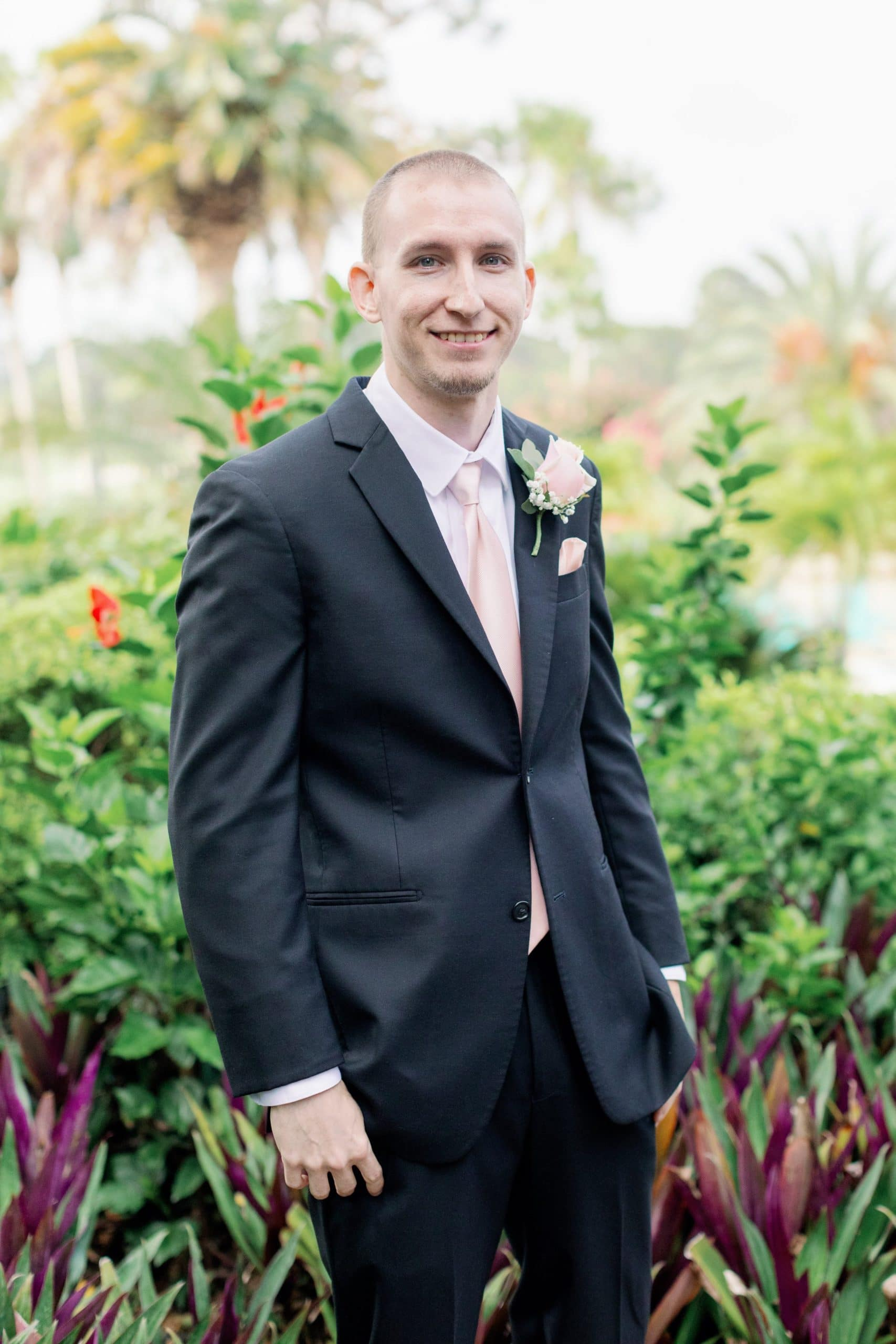Groom in tux in front of orange lilies