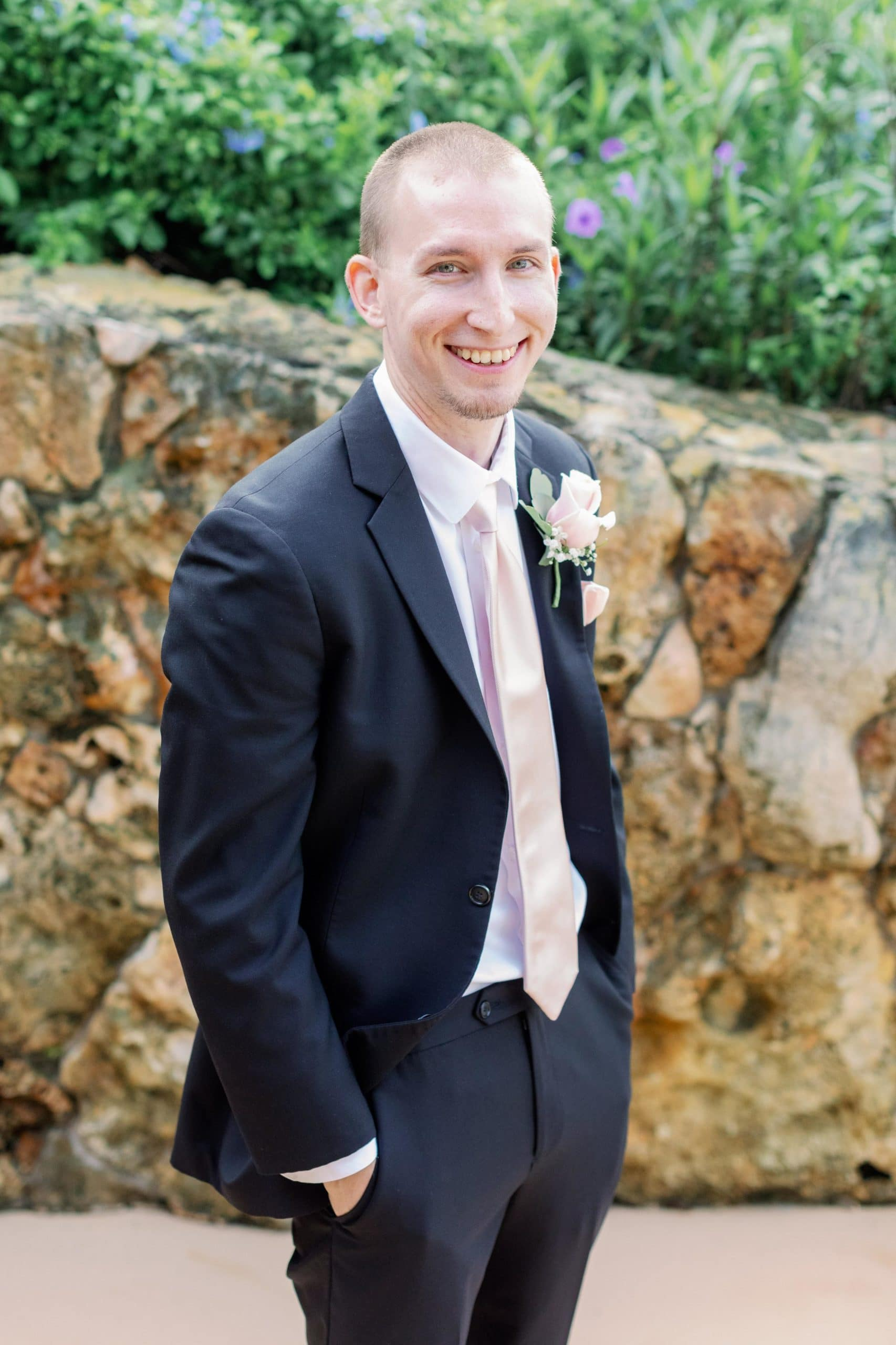 Groom in tux in front of stone wall