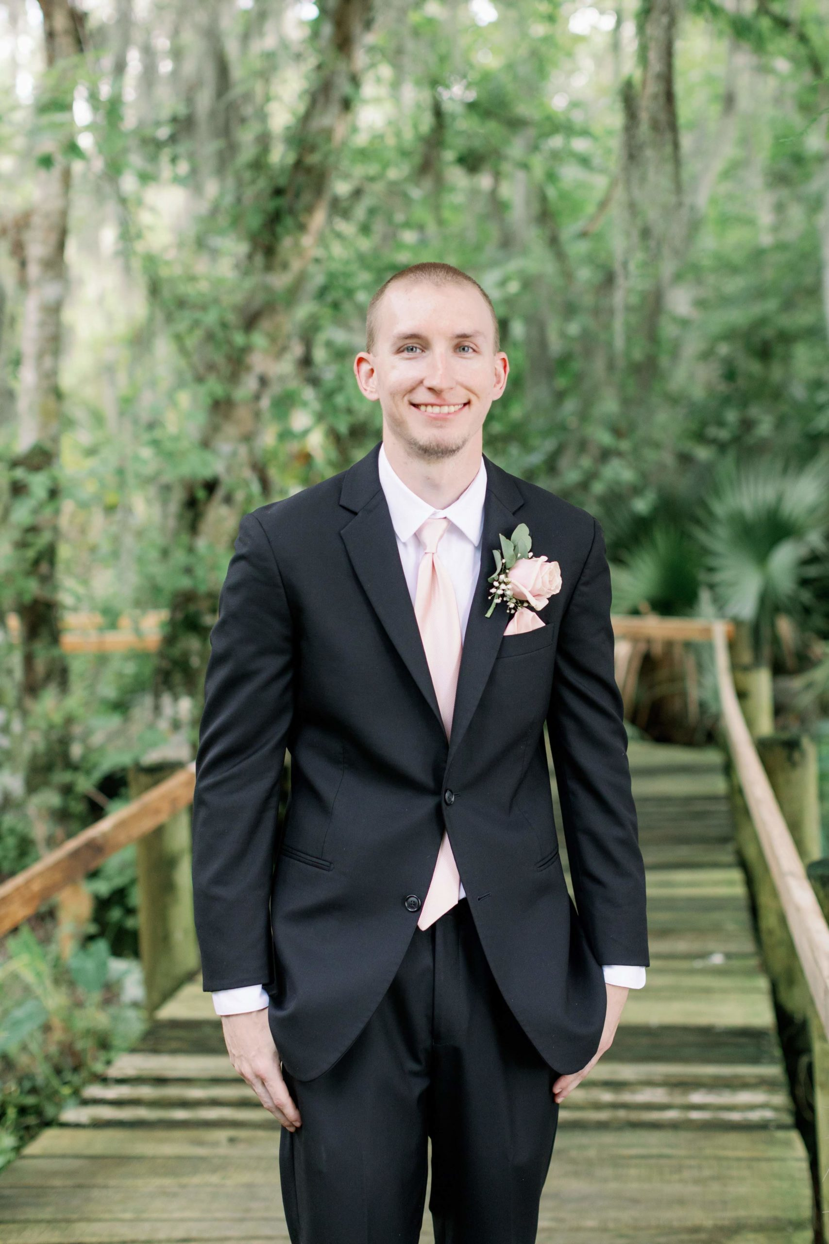 Groom by himself on wooden boardwalk