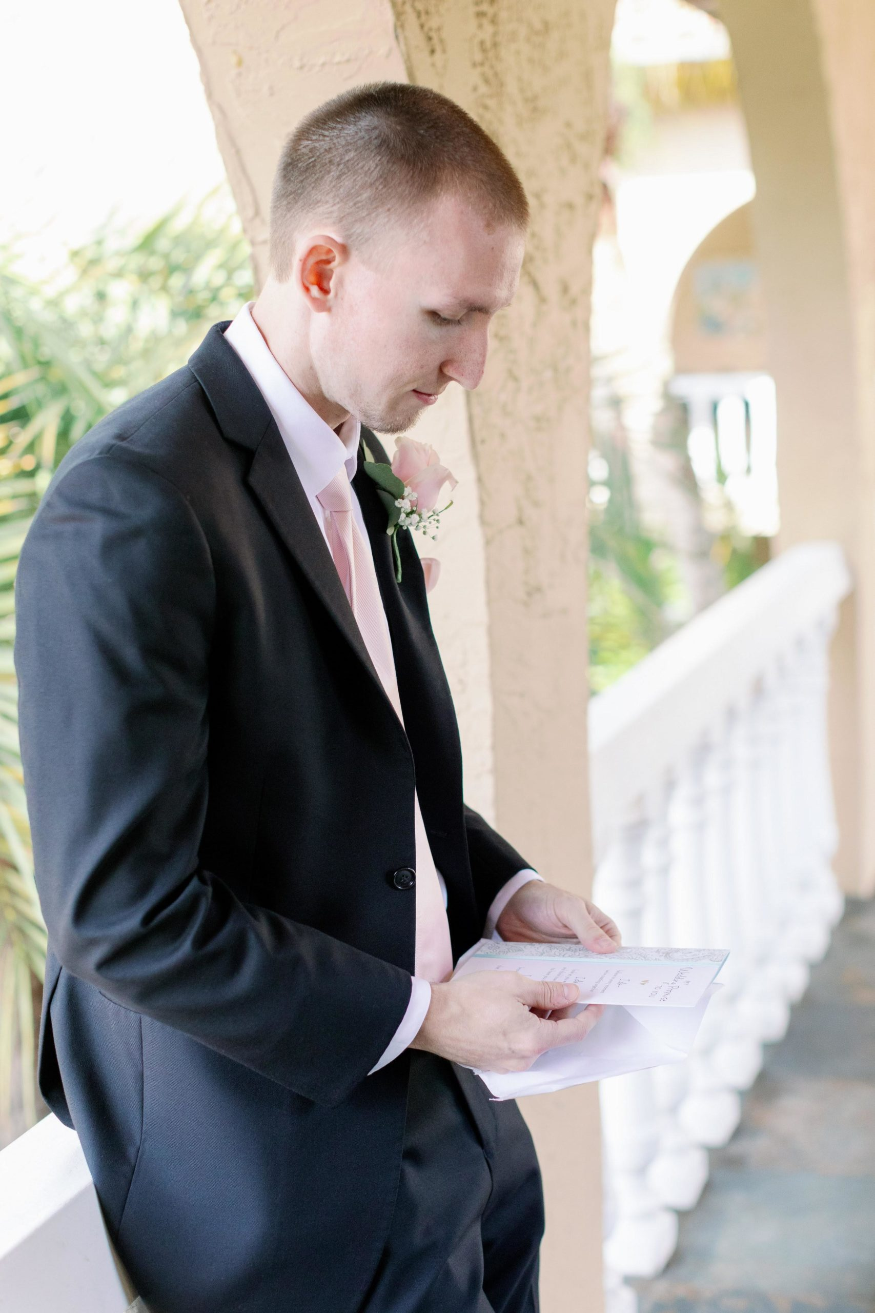 Groom sitting on white railing reading letter from bride