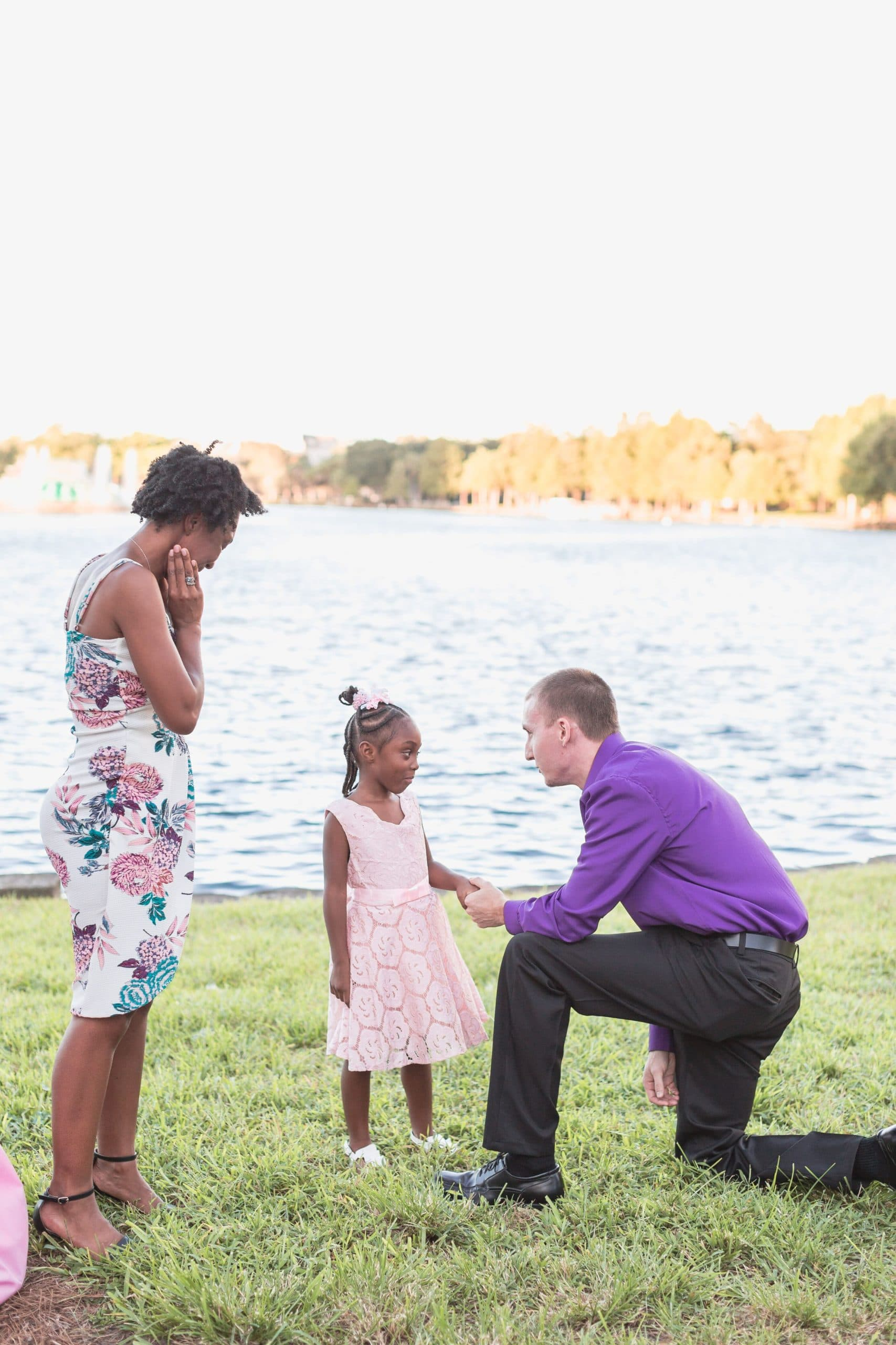 man in purple shirt on bended knee in front of lake proposing to daughter in pink dress