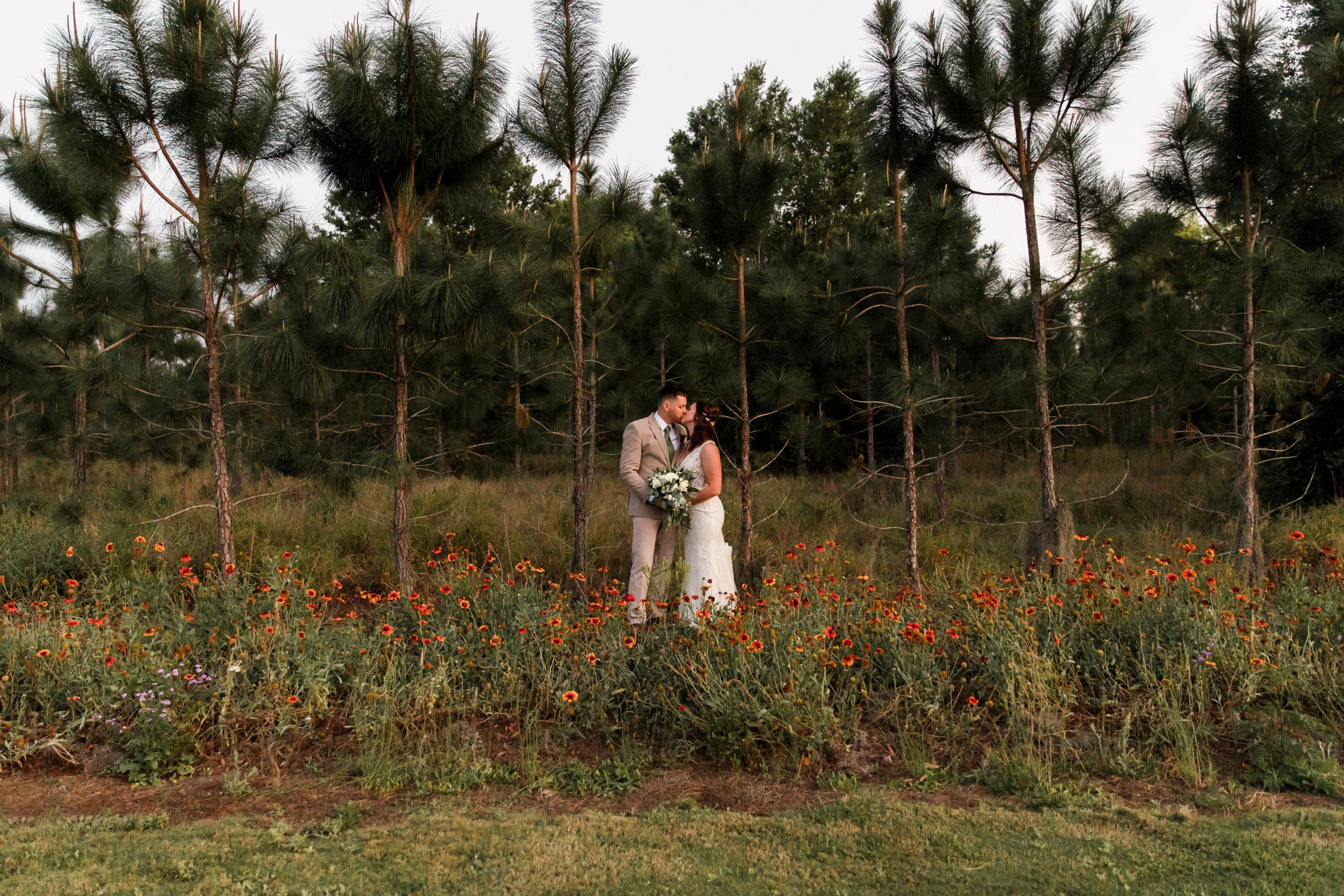 Bride and Groom standing in wildflowers