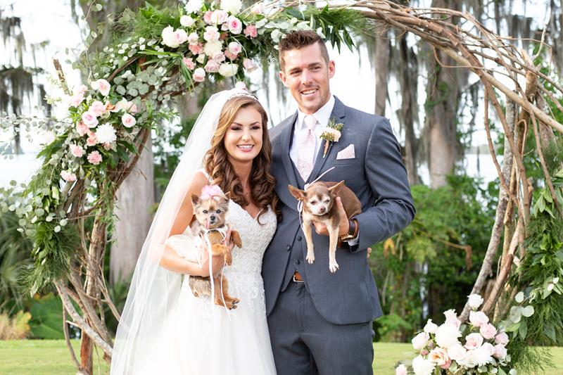 Bride and Groom with Fur Babies in front of infinity arch after choosing a wedding venue