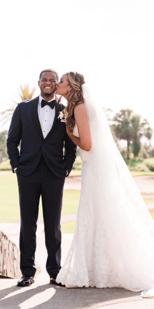 bride and groom kissing on stone bridge