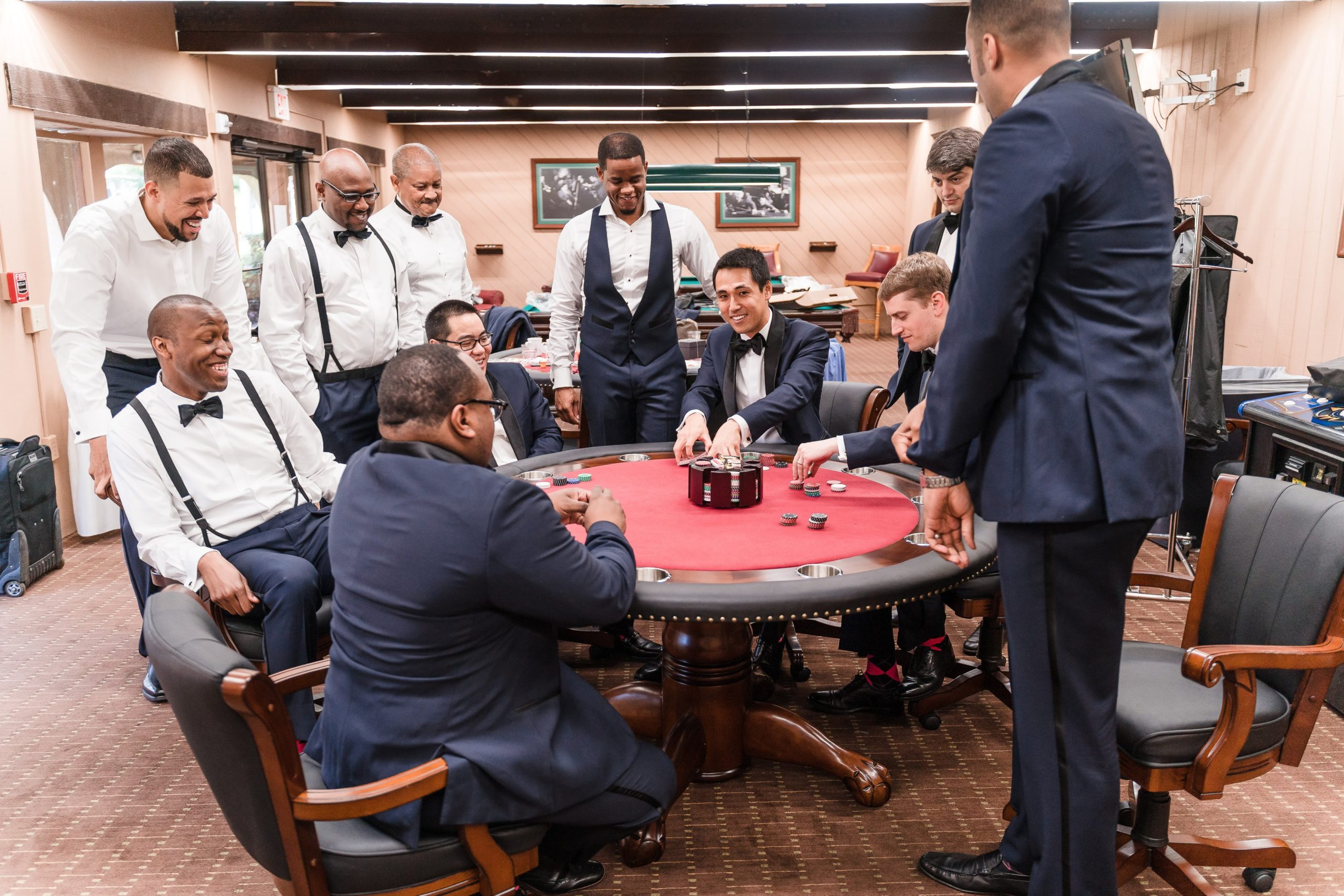 Groomsmen sitting around poker table playing poker