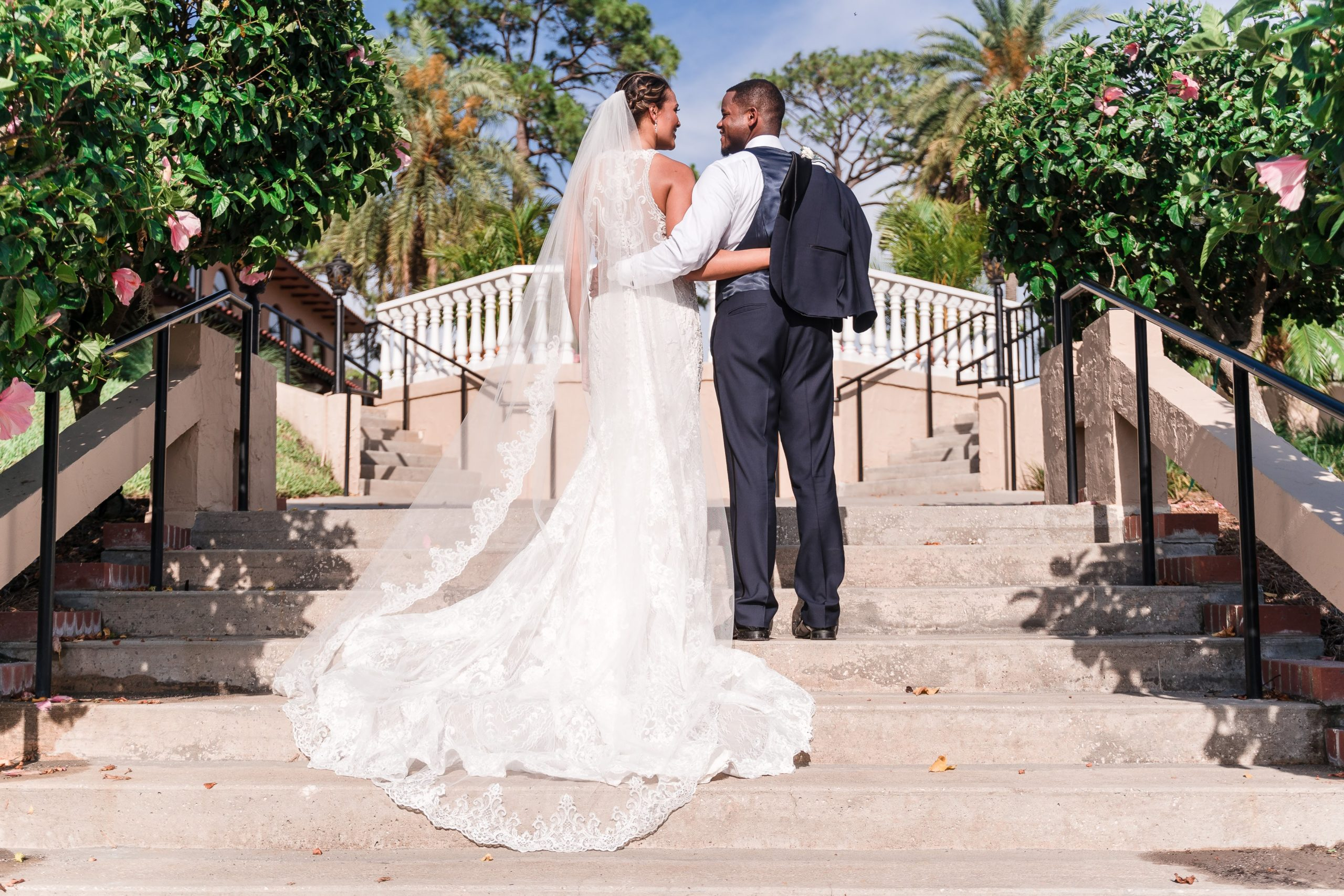 bride and groom on staircase with hibiscus