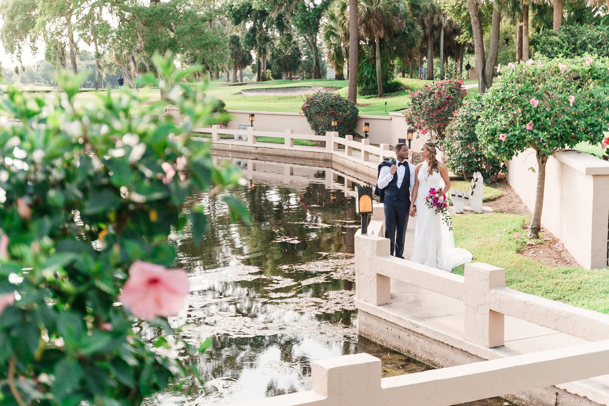 bride and groom walking on garden path next to lake