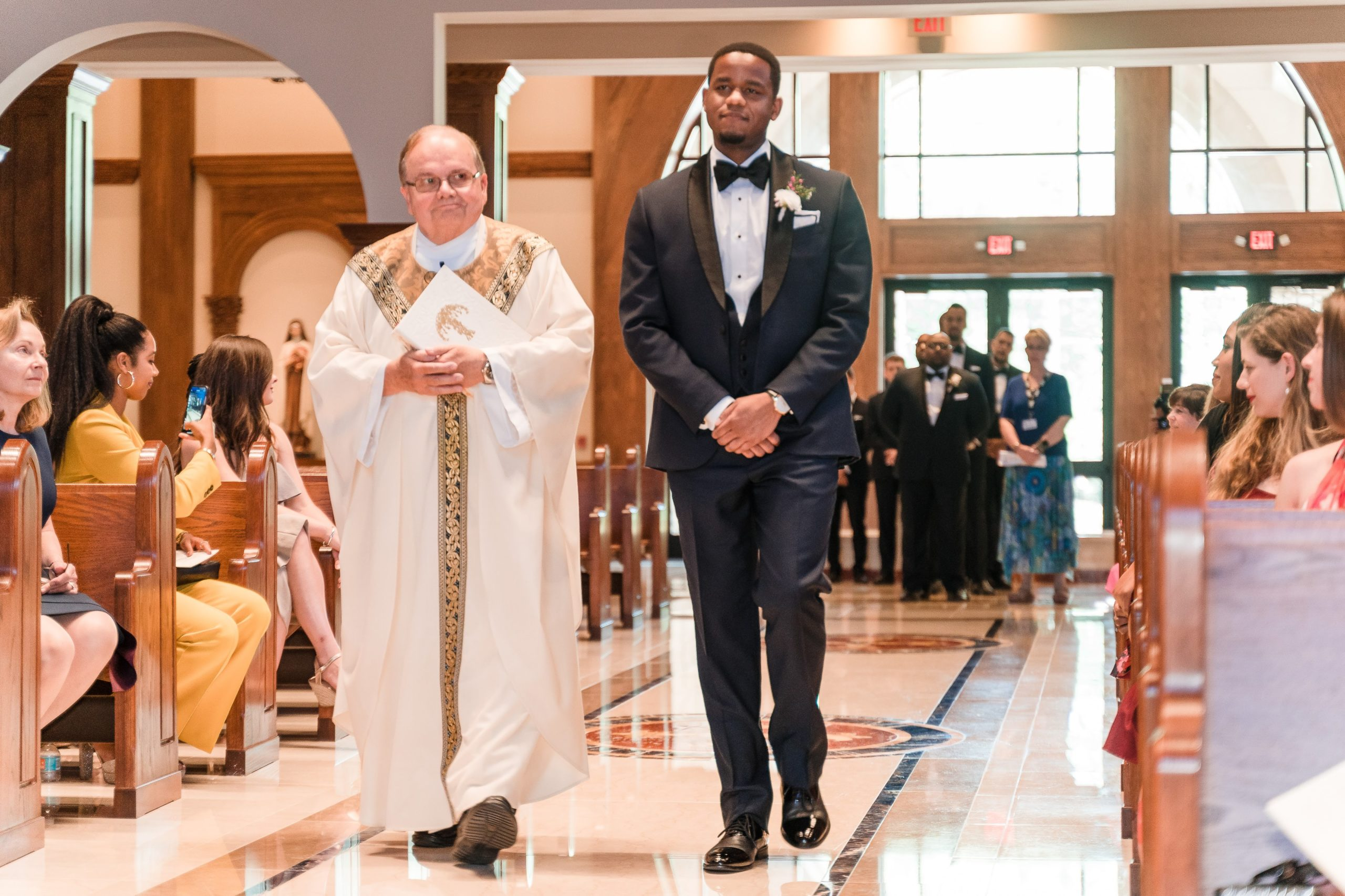 groom walking with priest