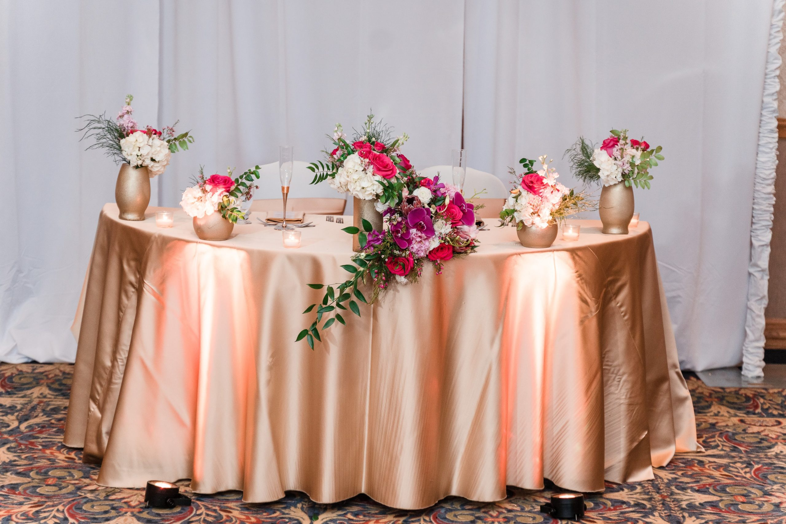 sweetheart table with gold linen and pink wedding flowers in orlando ballroom