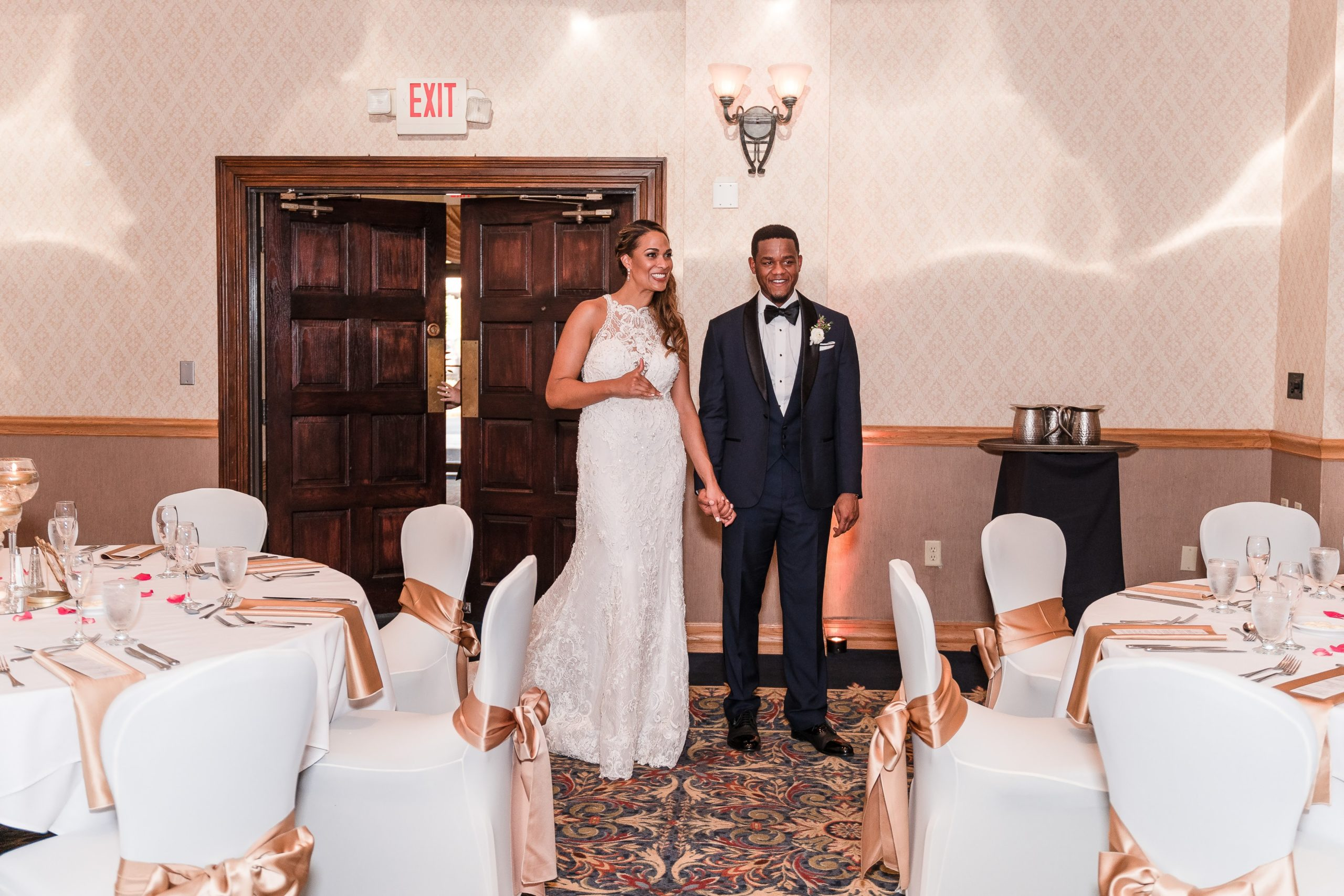 bride and groom holding hands entering gold and white wedding in orlando ballroom