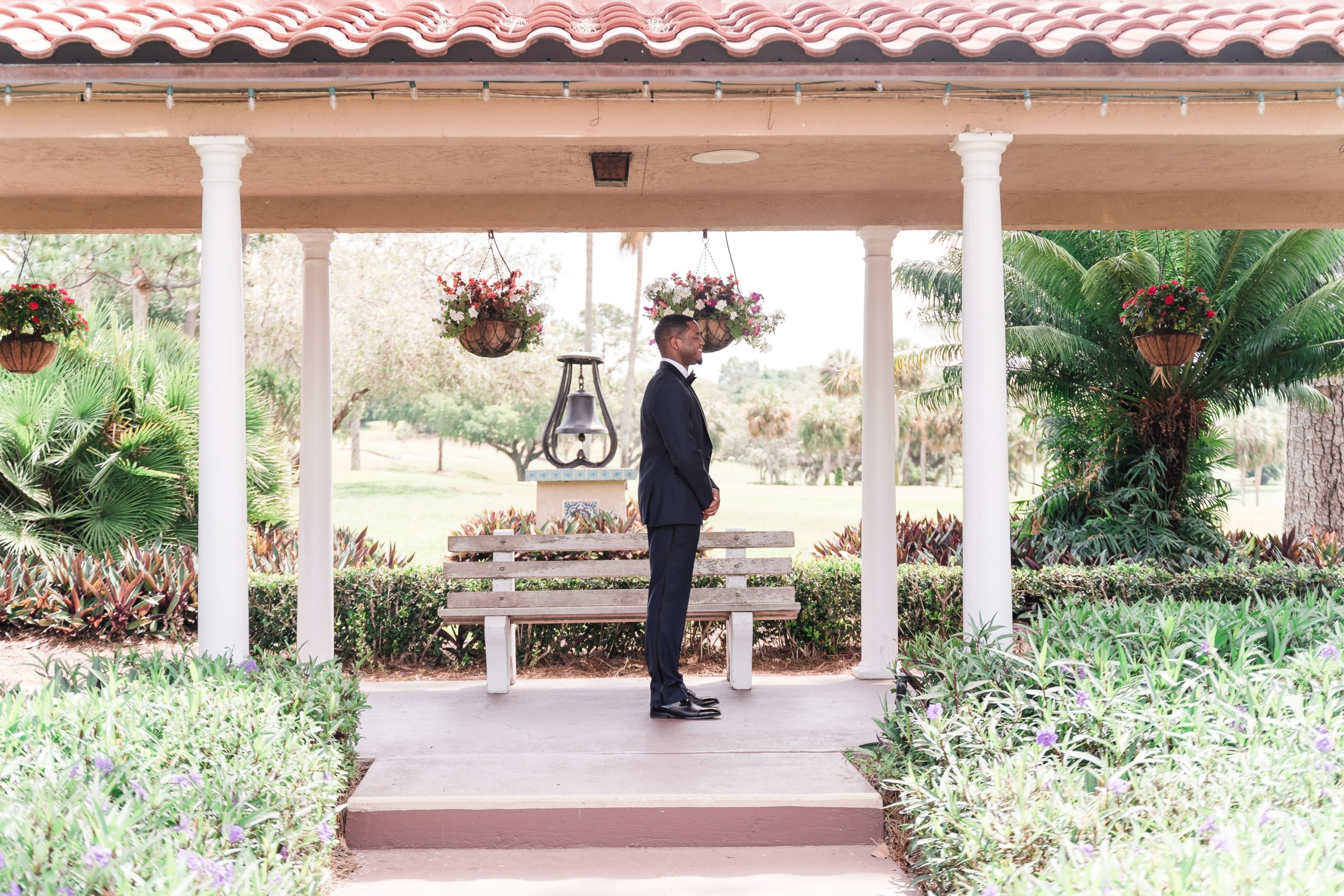 groom waiting between columns in front of bench for his bride