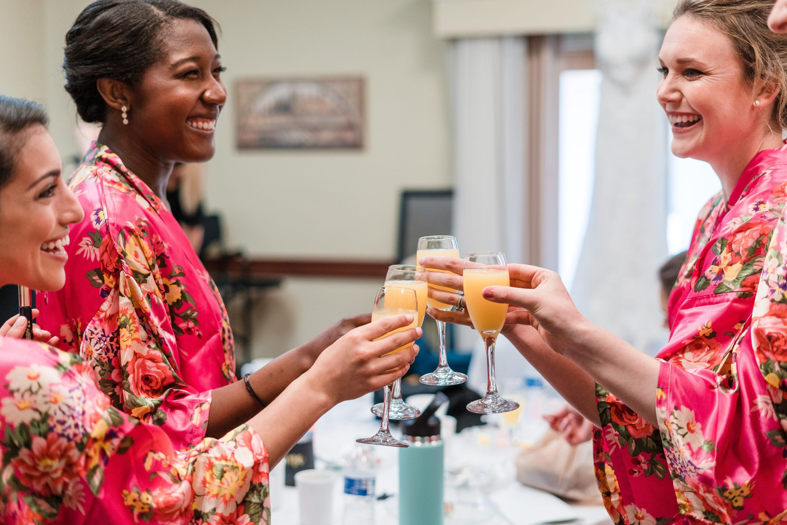 Bridesmaids and bride clinking together mimosas