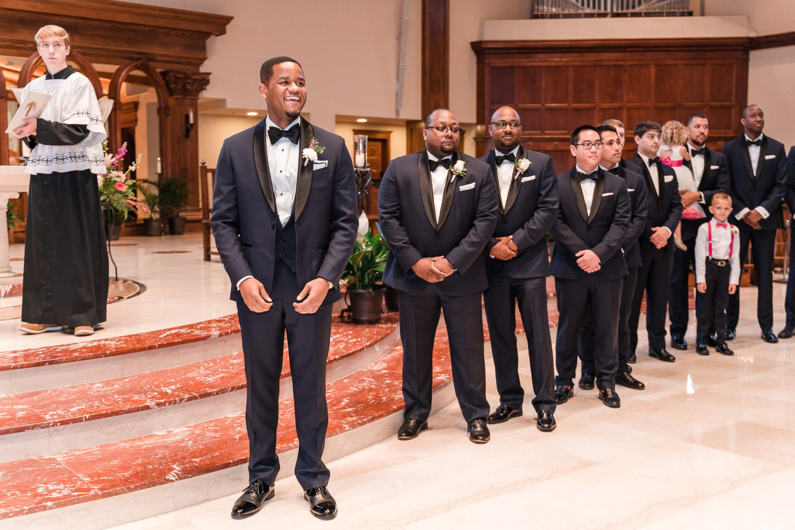 groom and groomsmen waiting at the alter