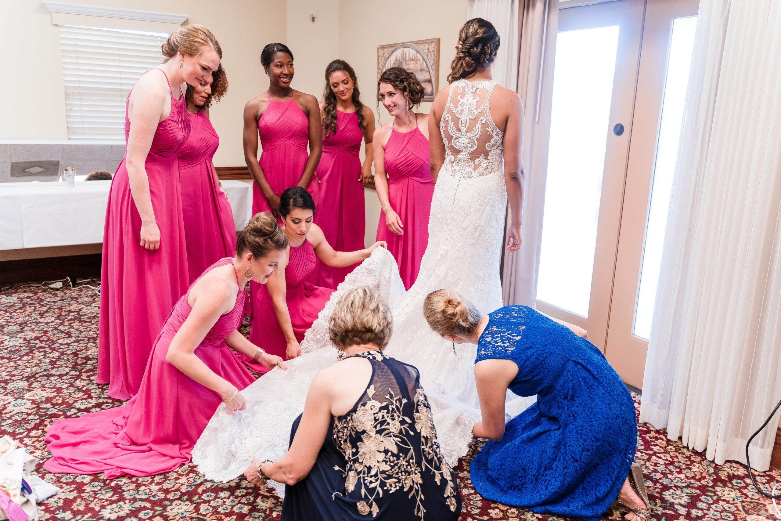 bridesmaids in pink gowns with mother of bride fixing brides dress