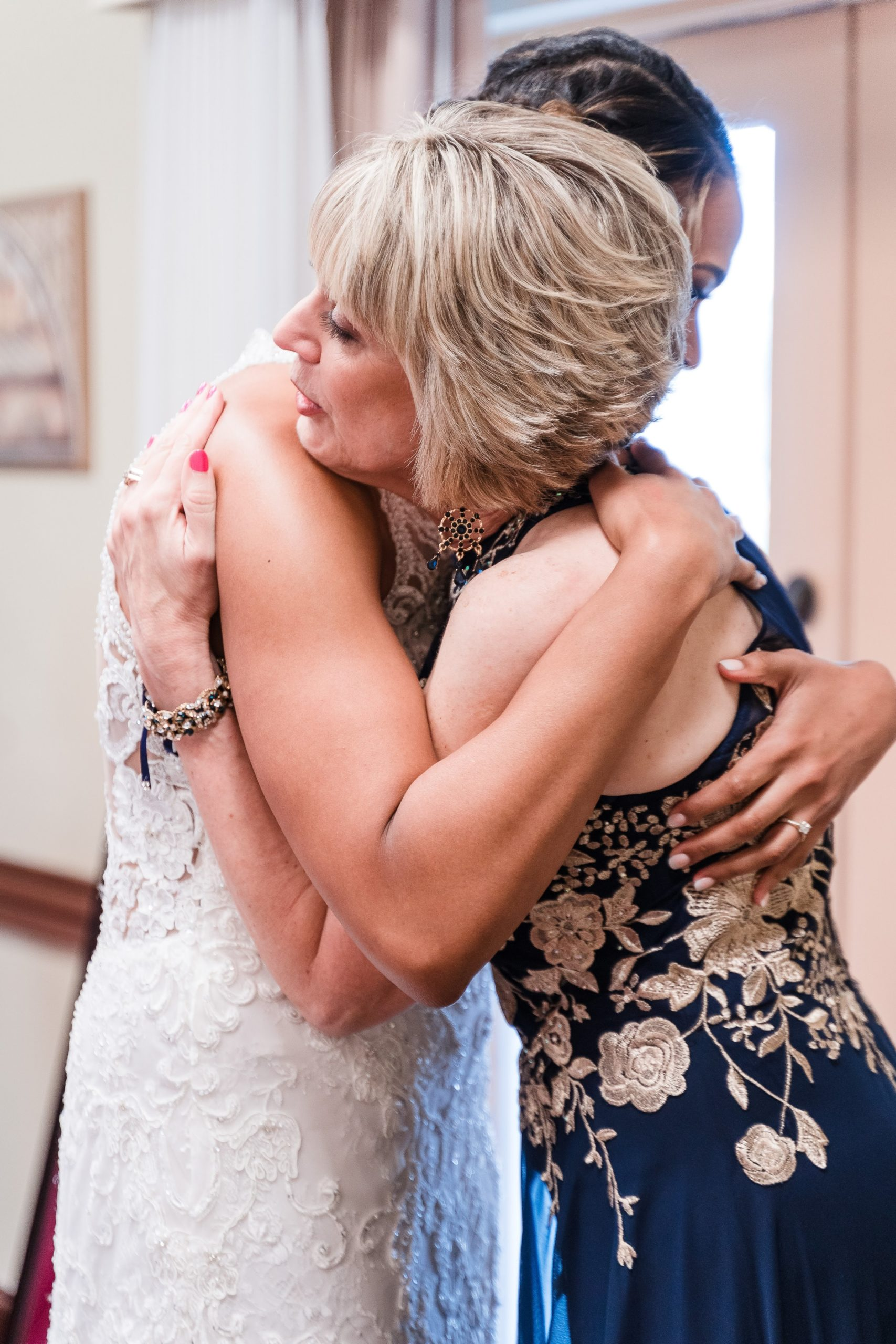 mother of bride hugging mom