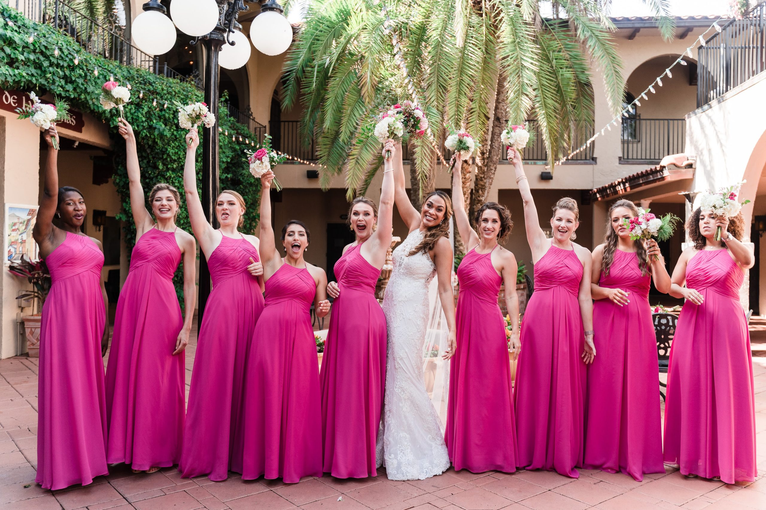 pink dresses on bridesmaids with bride holding flowers in the air