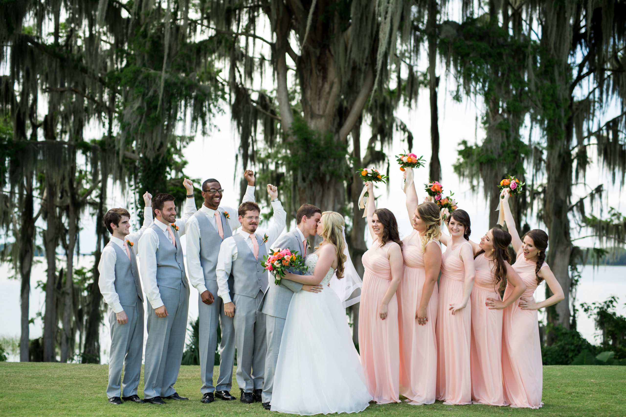 Groomsmen in grey and bridesmaids in coral with bride and groom kissing featuring shelby crane catering manager