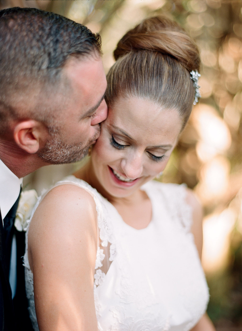 Groom Kissing Bride with High Bun