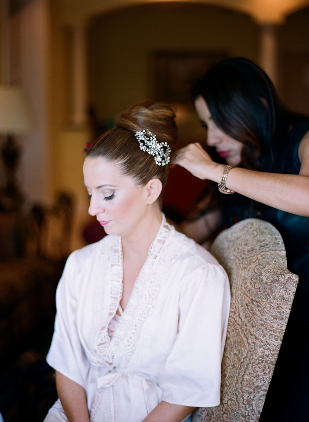 Bride sitting getting her bridal high bun styled