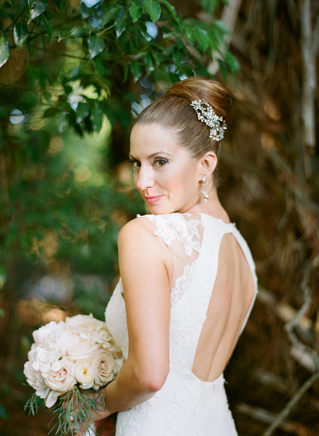 bride posing in front of greenery with elegant high bun