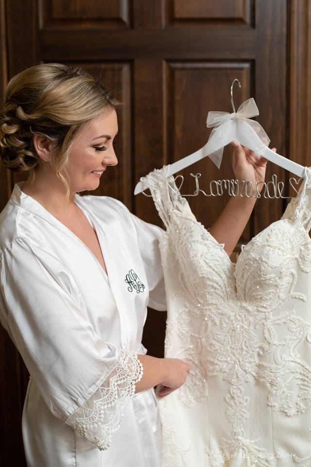 bride looking at her wedding dress with a gorgeous updo bridal hair style