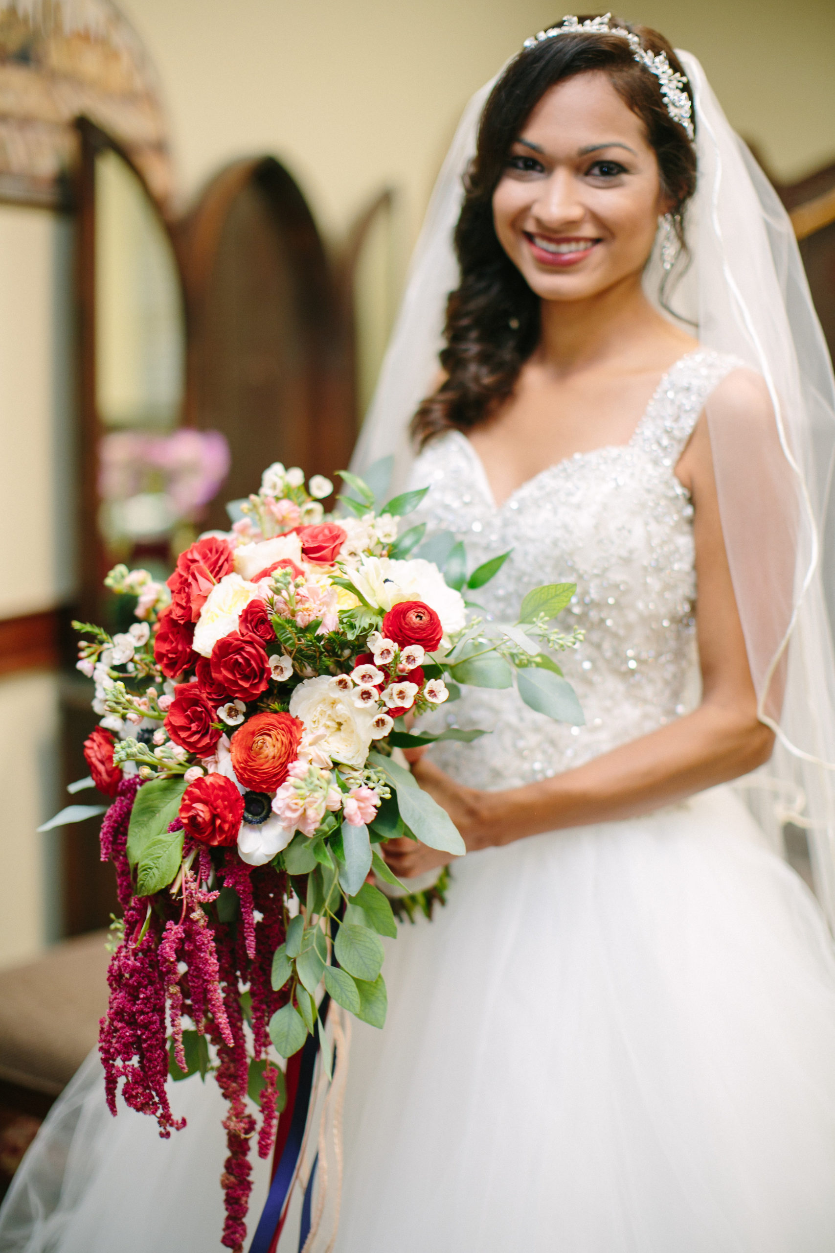 bride smiling in front of ready room mirror with side swept do hair style