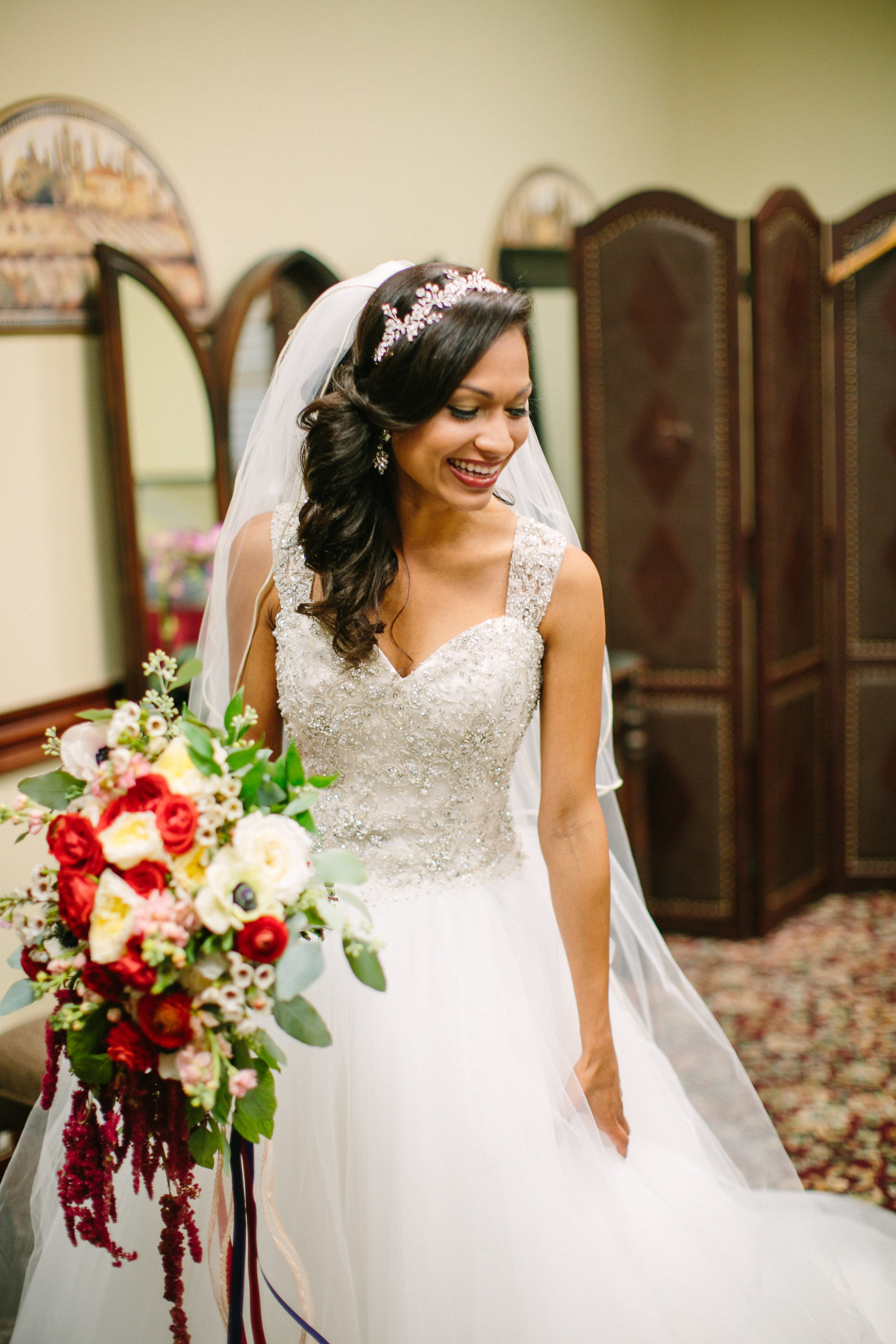 Bride smiling in wedding dress with side swept bridal hair style