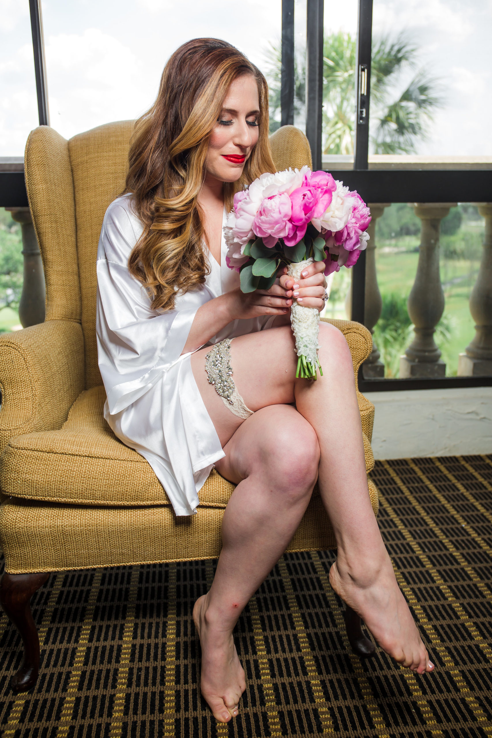 Bride sitting in chair holding bridal bouquet with gorgeous soft curls