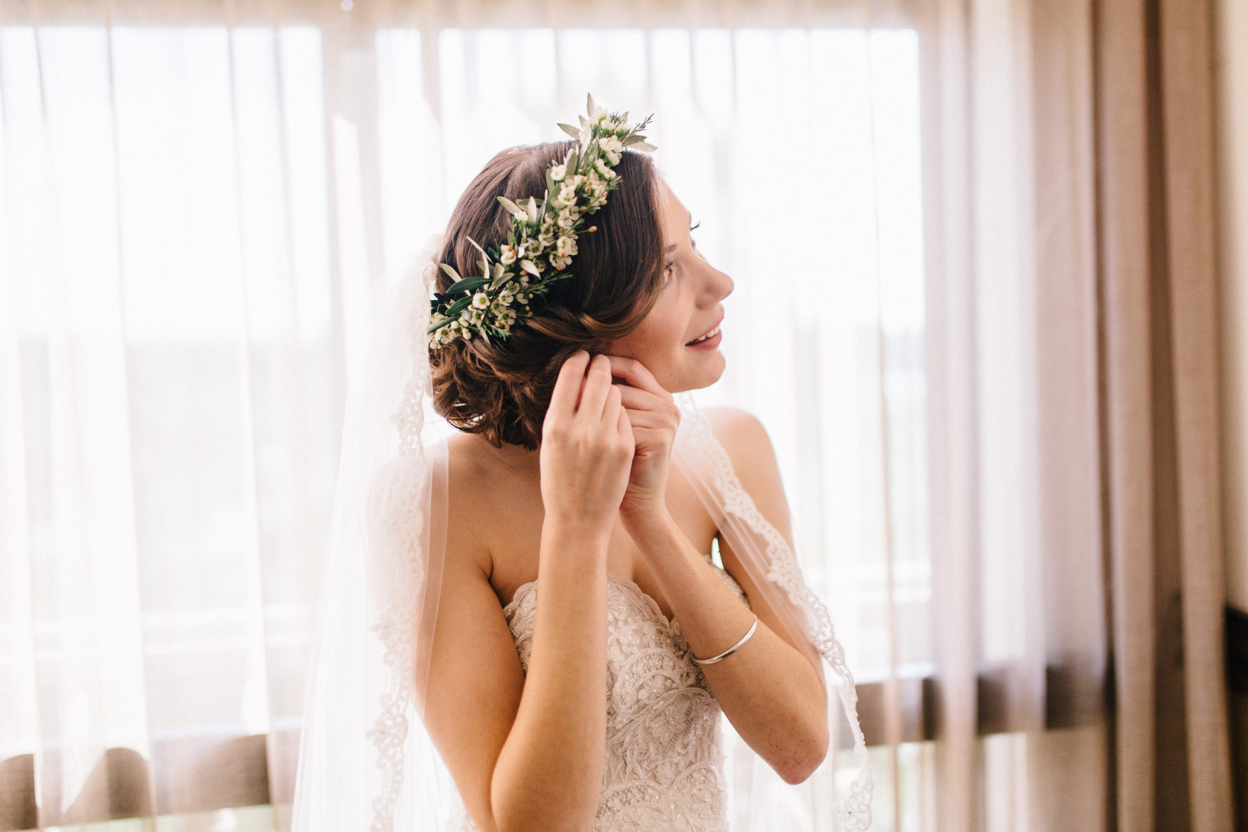 Bride with stylish updo hairstyle putting earrings in