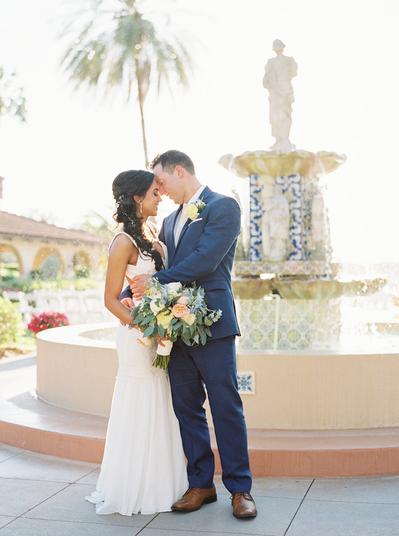 Groom kissing bride in front of spanish tile fountain