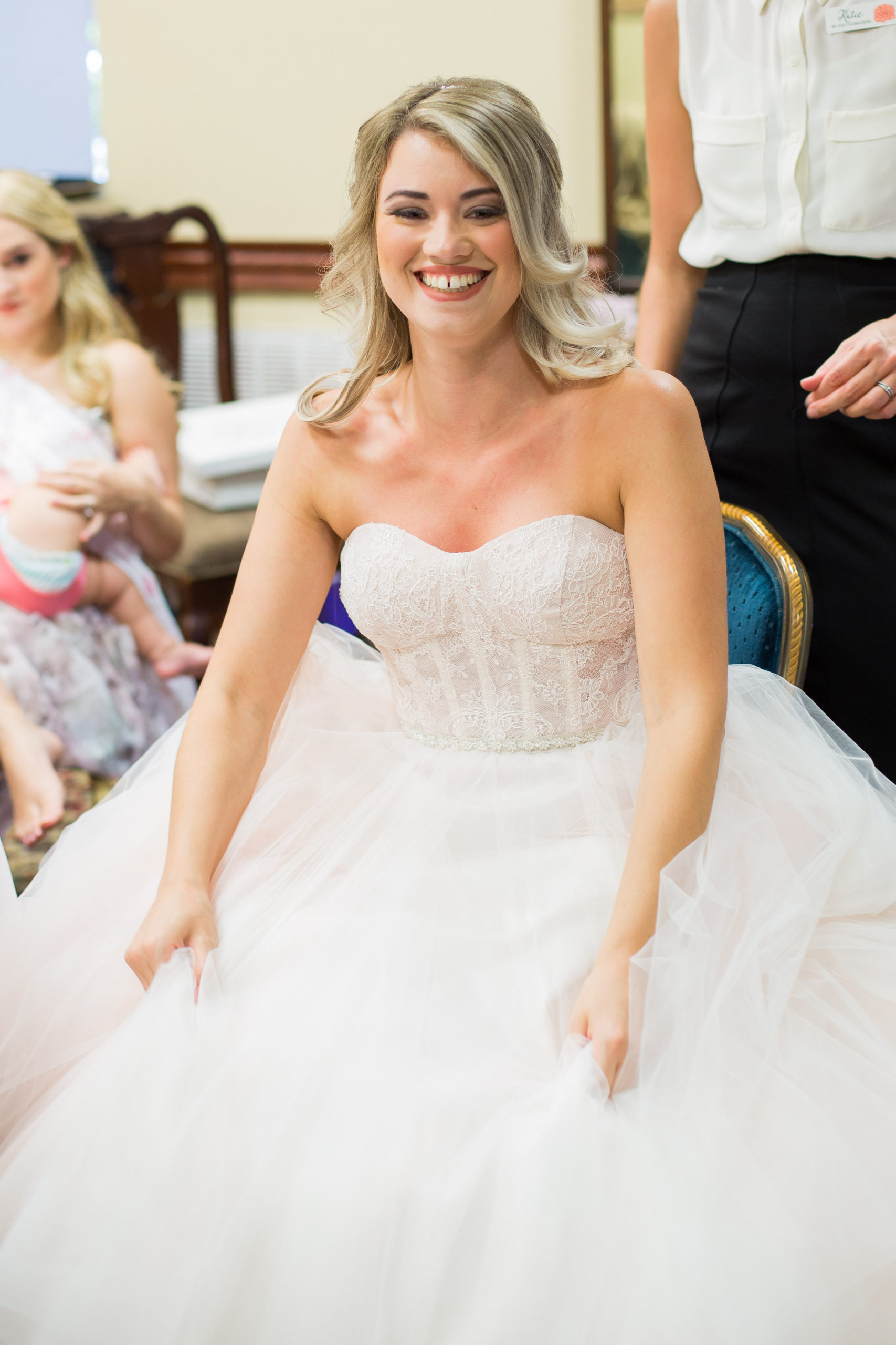bride sitting on a blue chair in her wedding dress smiling