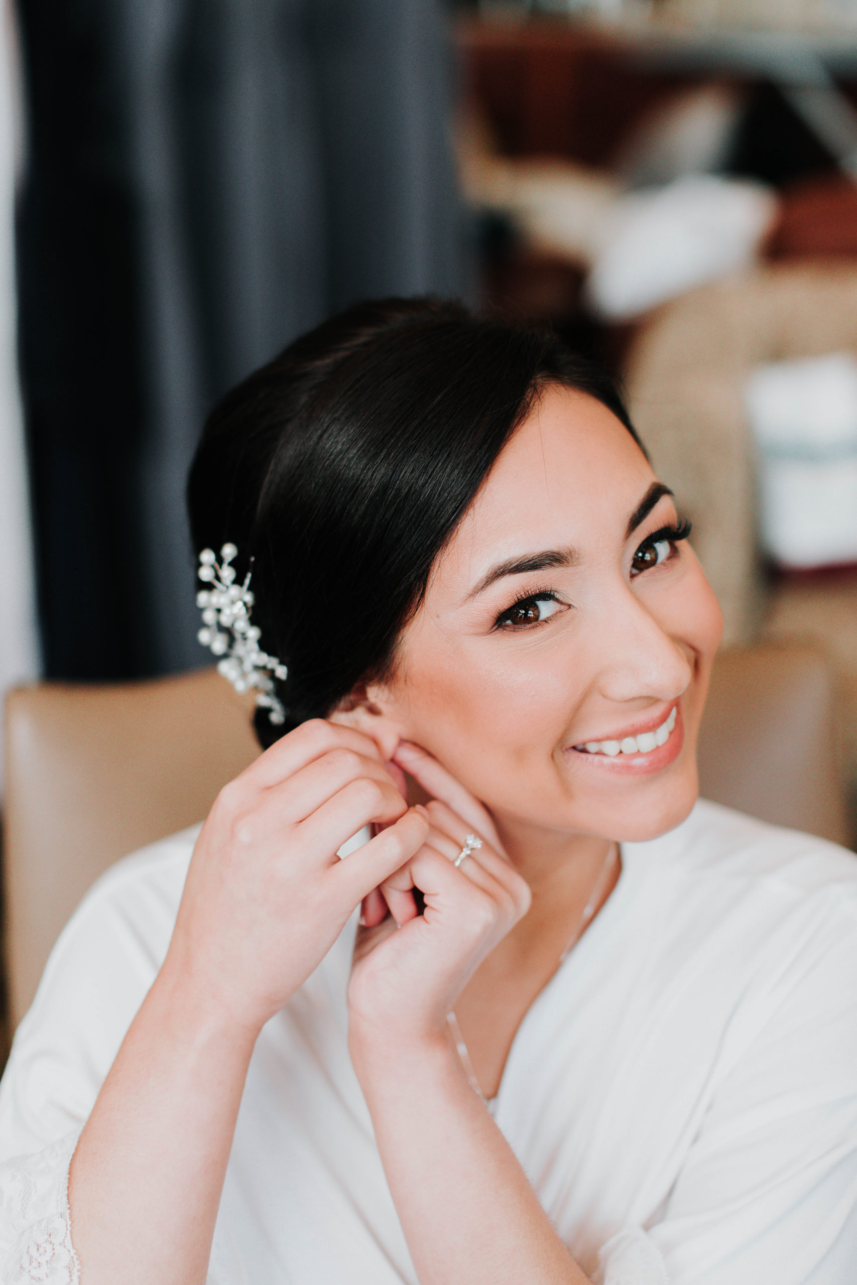 bride smiling while putting her earrings in