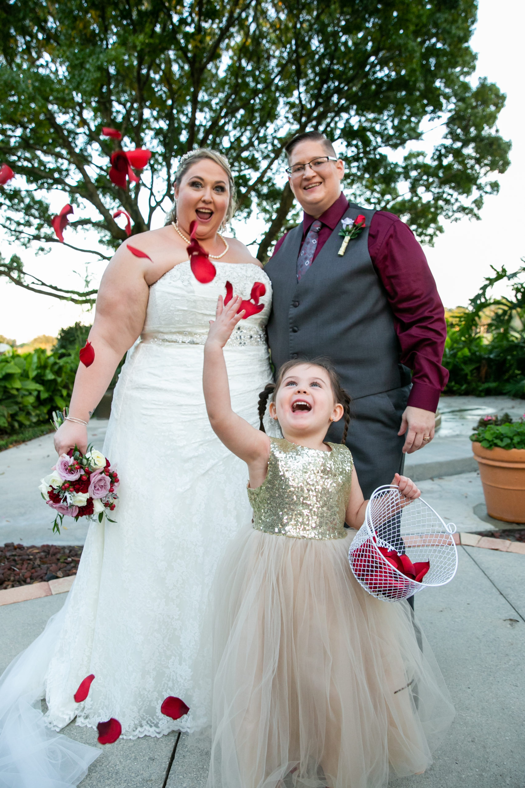Flower Girl Throwing Rose Petals after Ceremony in front of two Brides