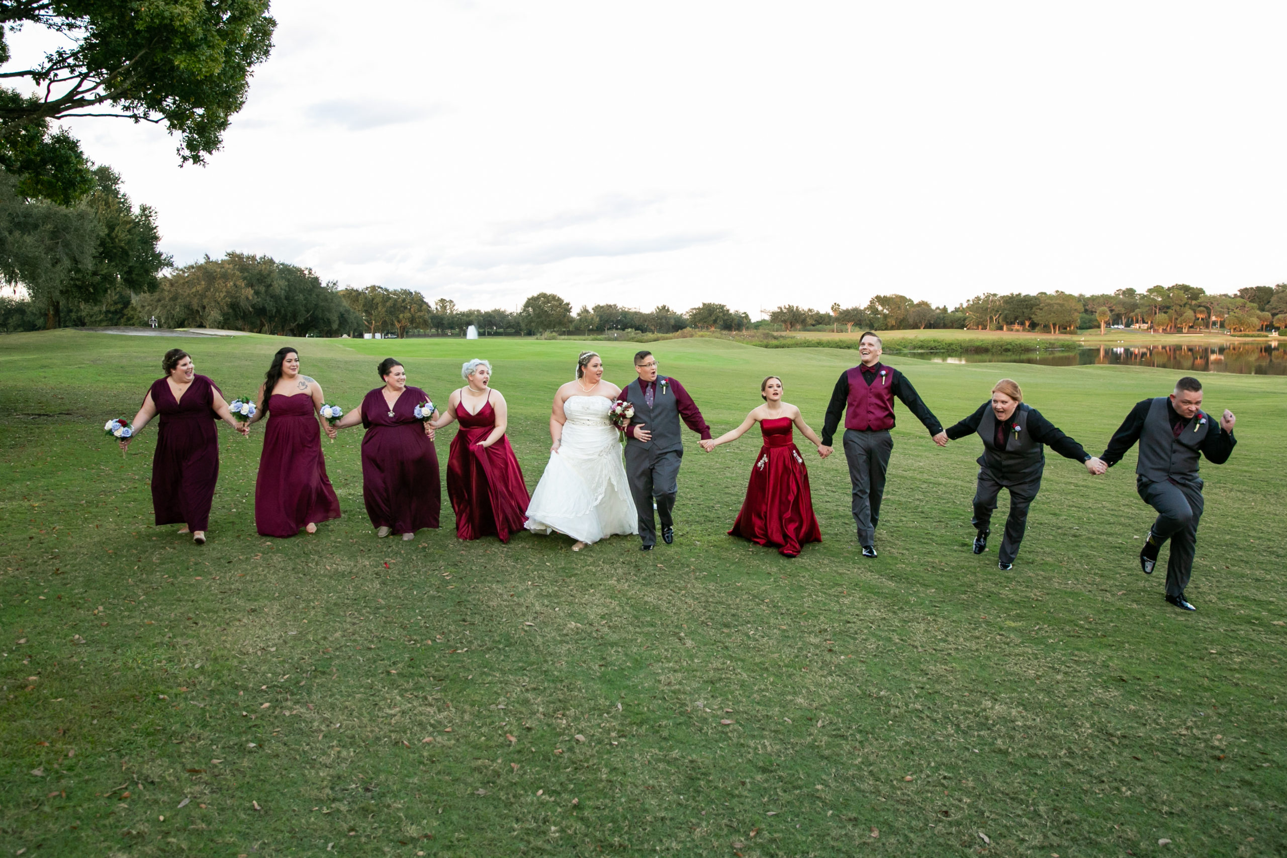 bridal party all holding hands together