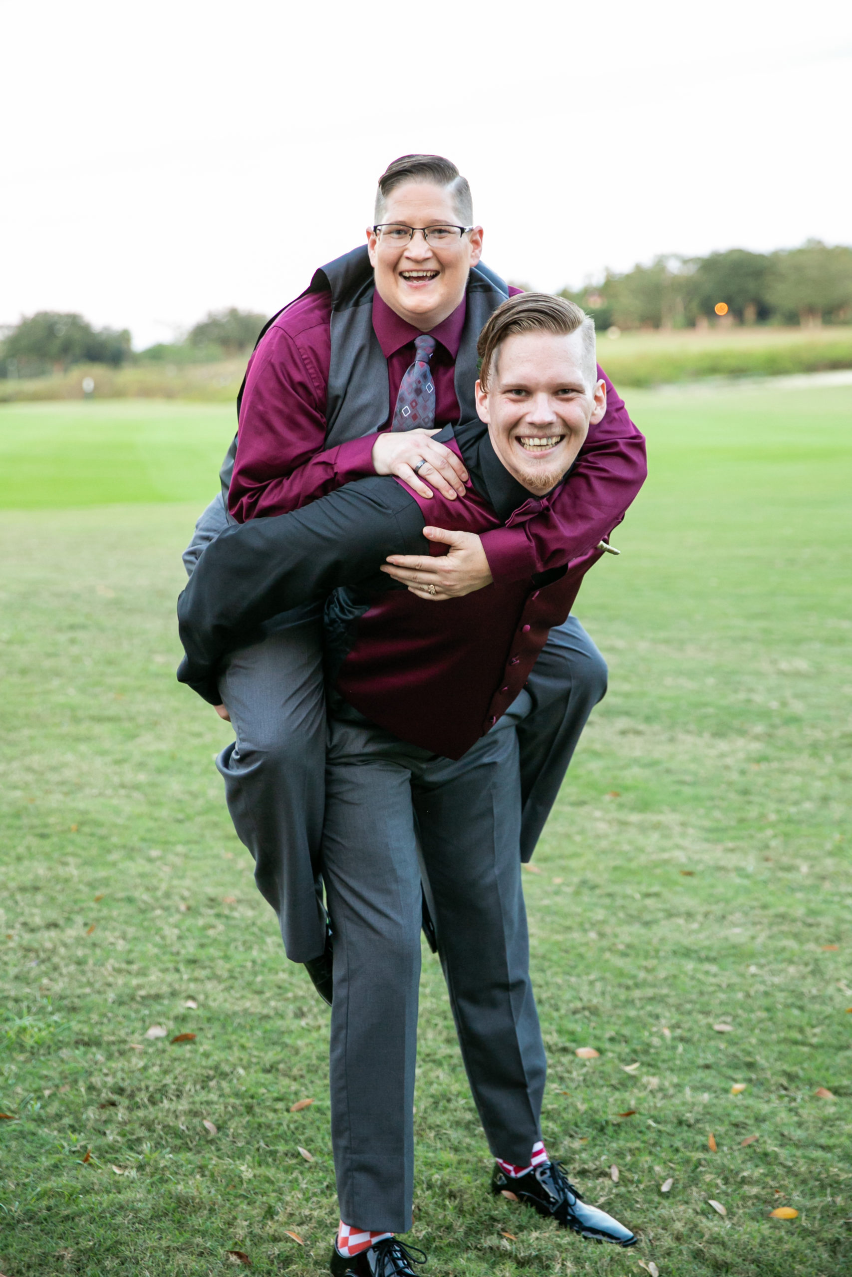 brother of bride giving the bride a piggy back ride