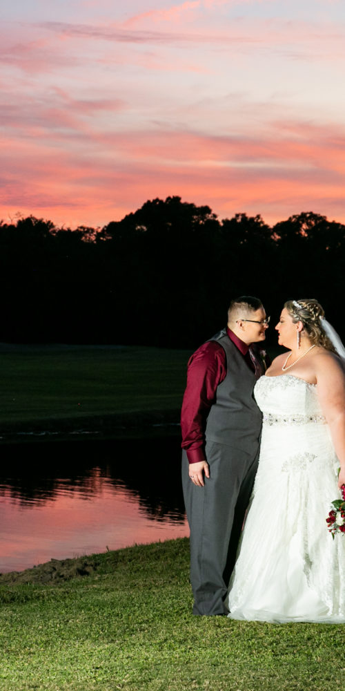 brides in front of lake at sunset