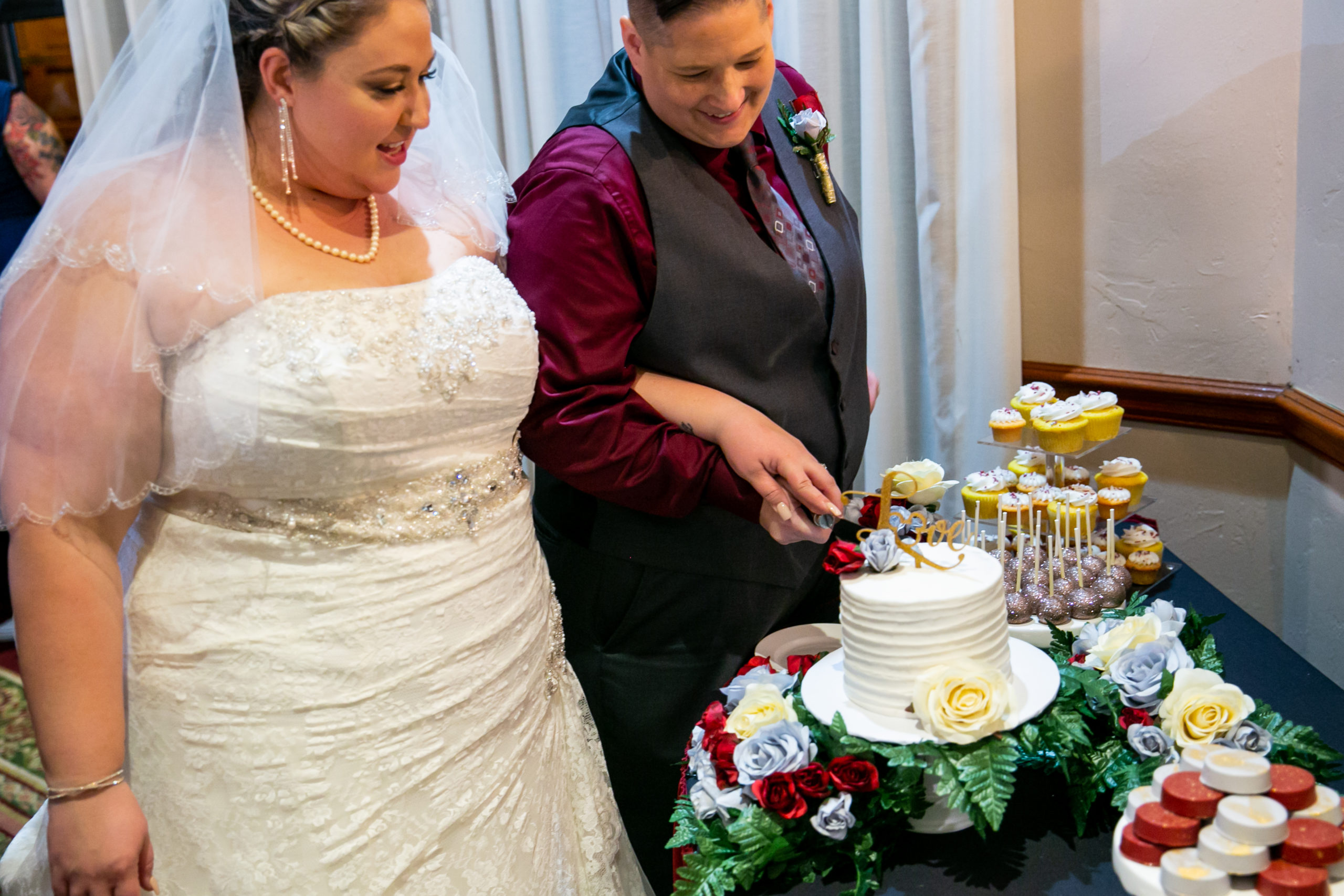two brides cutting wedding cake