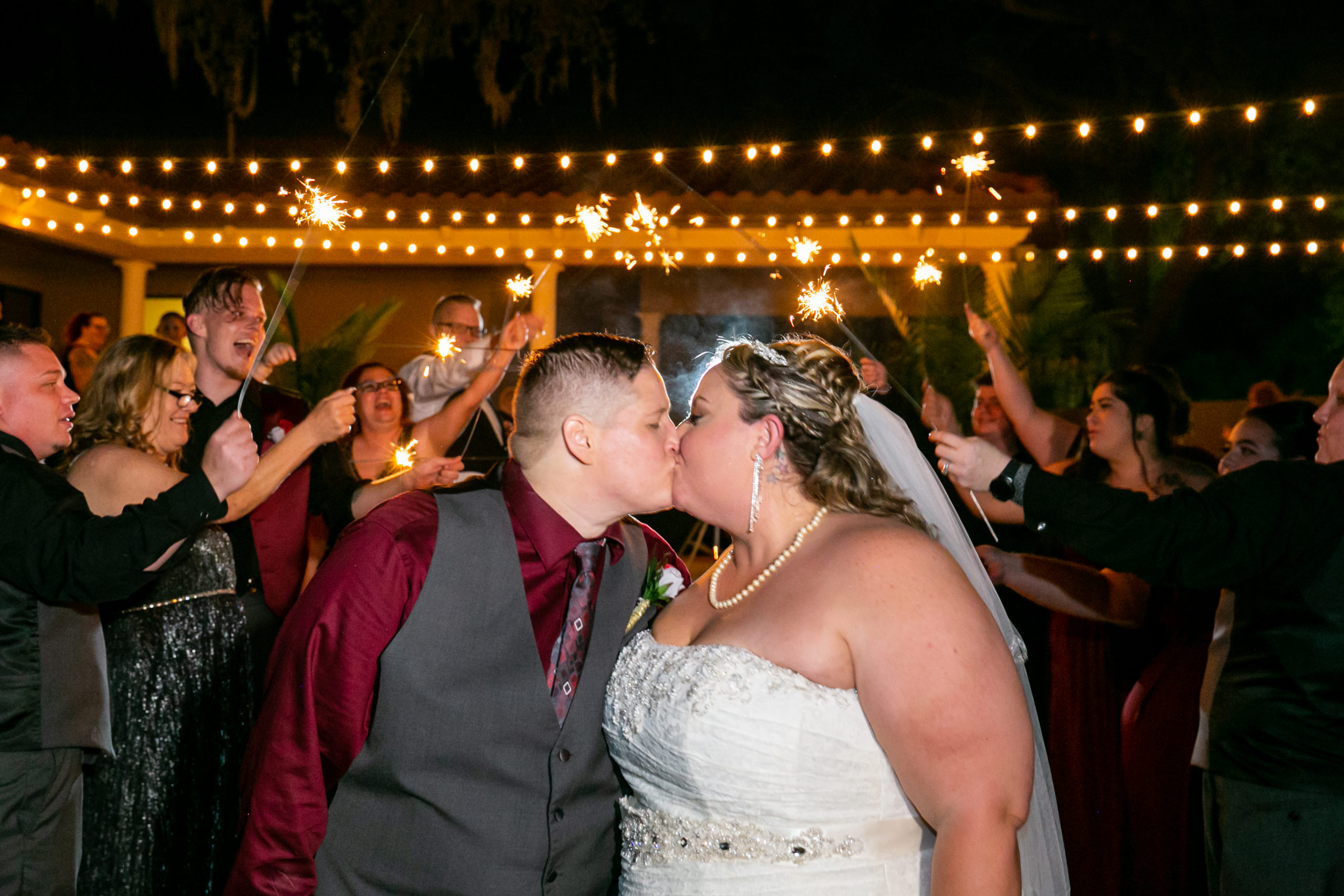 Close up of two brides kissing during sparkler exit